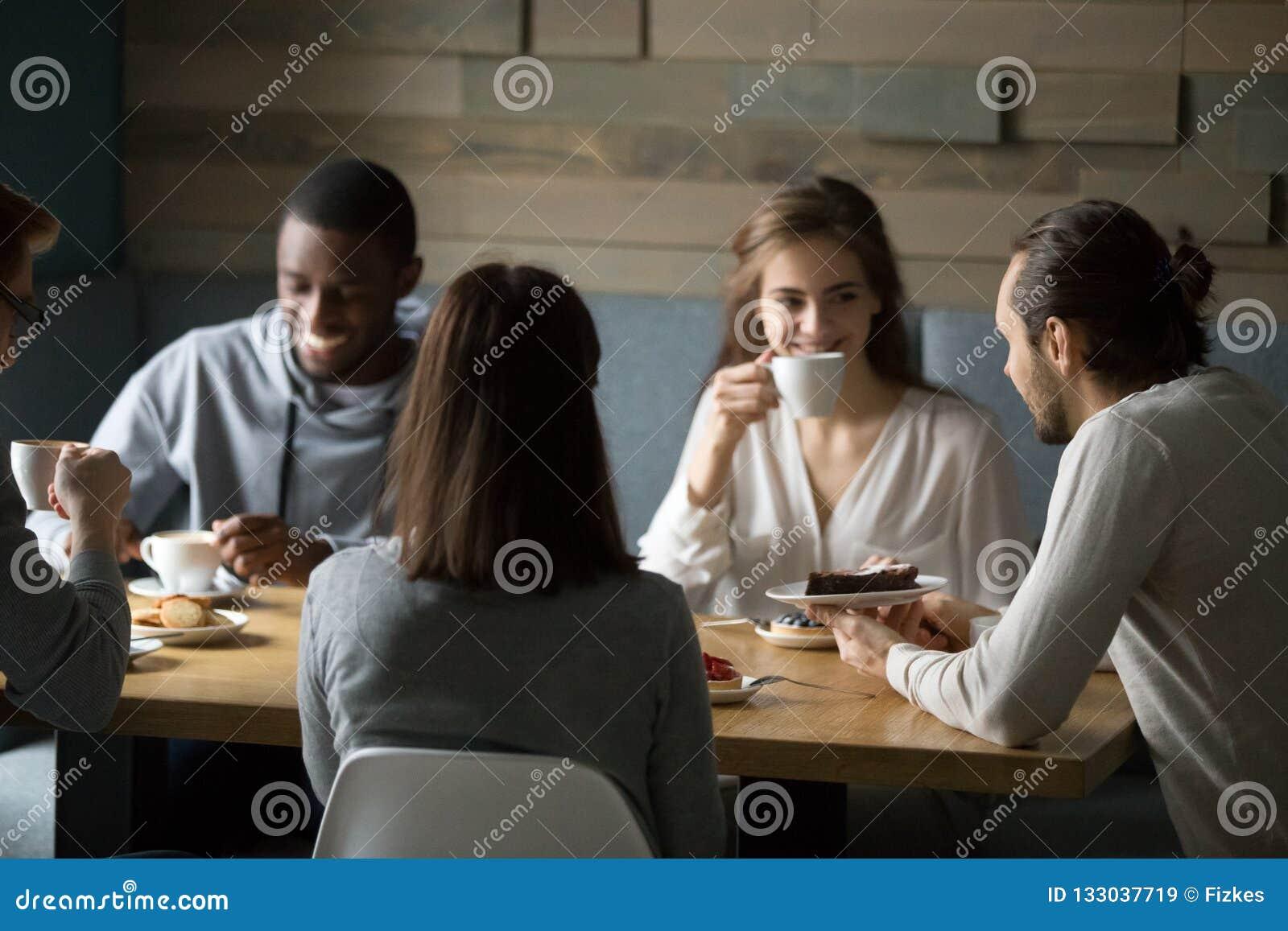 享用咖啡和点心在咖啡馆的微笑的不同的朋友
