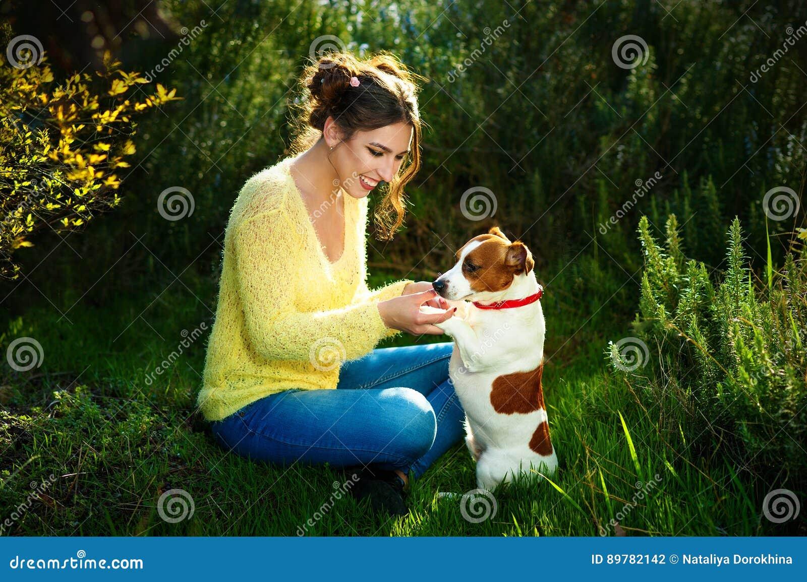 享用在公园的美丽的年轻深色的妇女户外与她华美的杰克罗素狗一起-坐