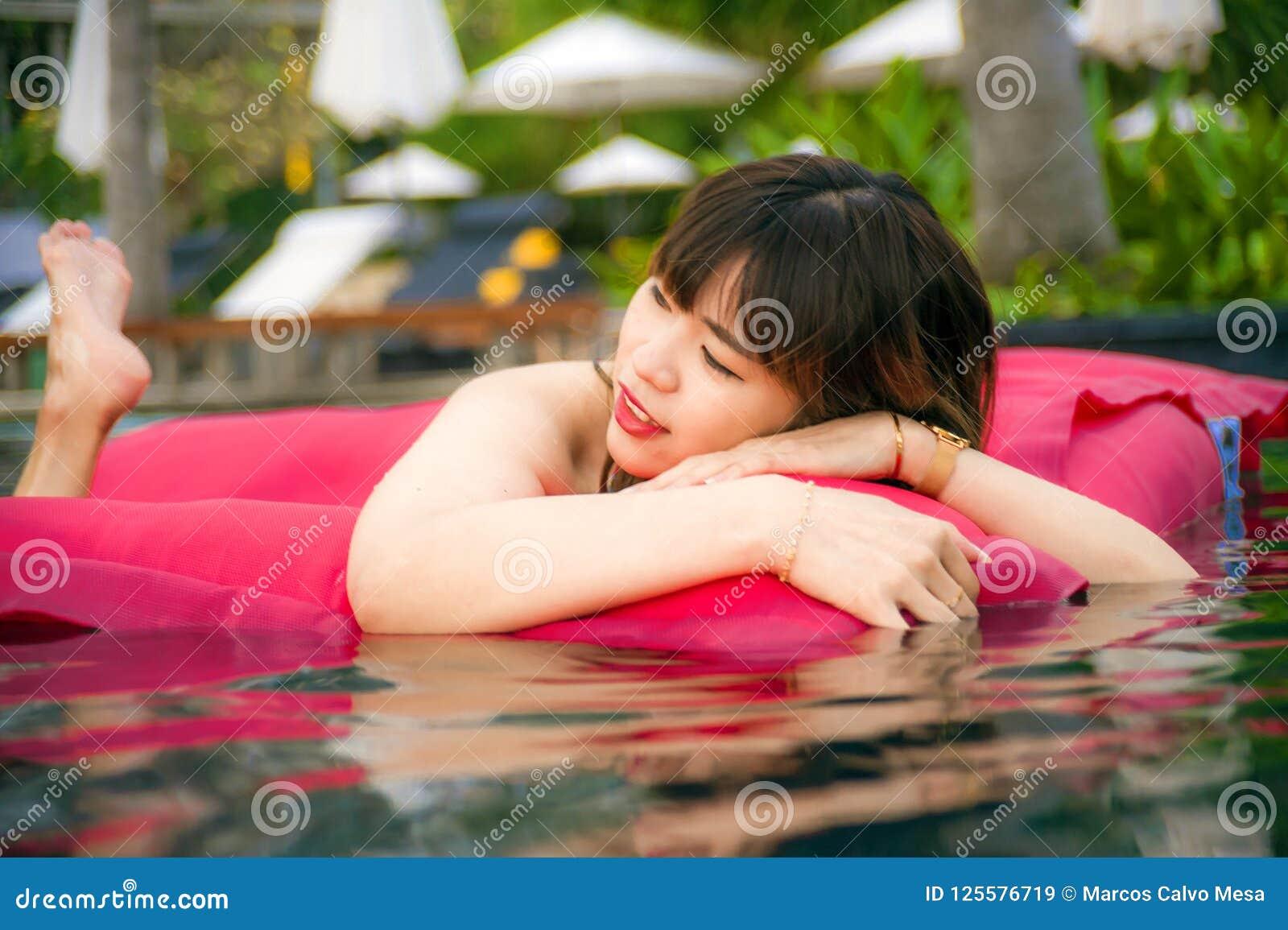 享用在度假胜地游泳池的年轻愉快和可爱的亚裔中国妇女获得乐趣在airbed微笑快乐