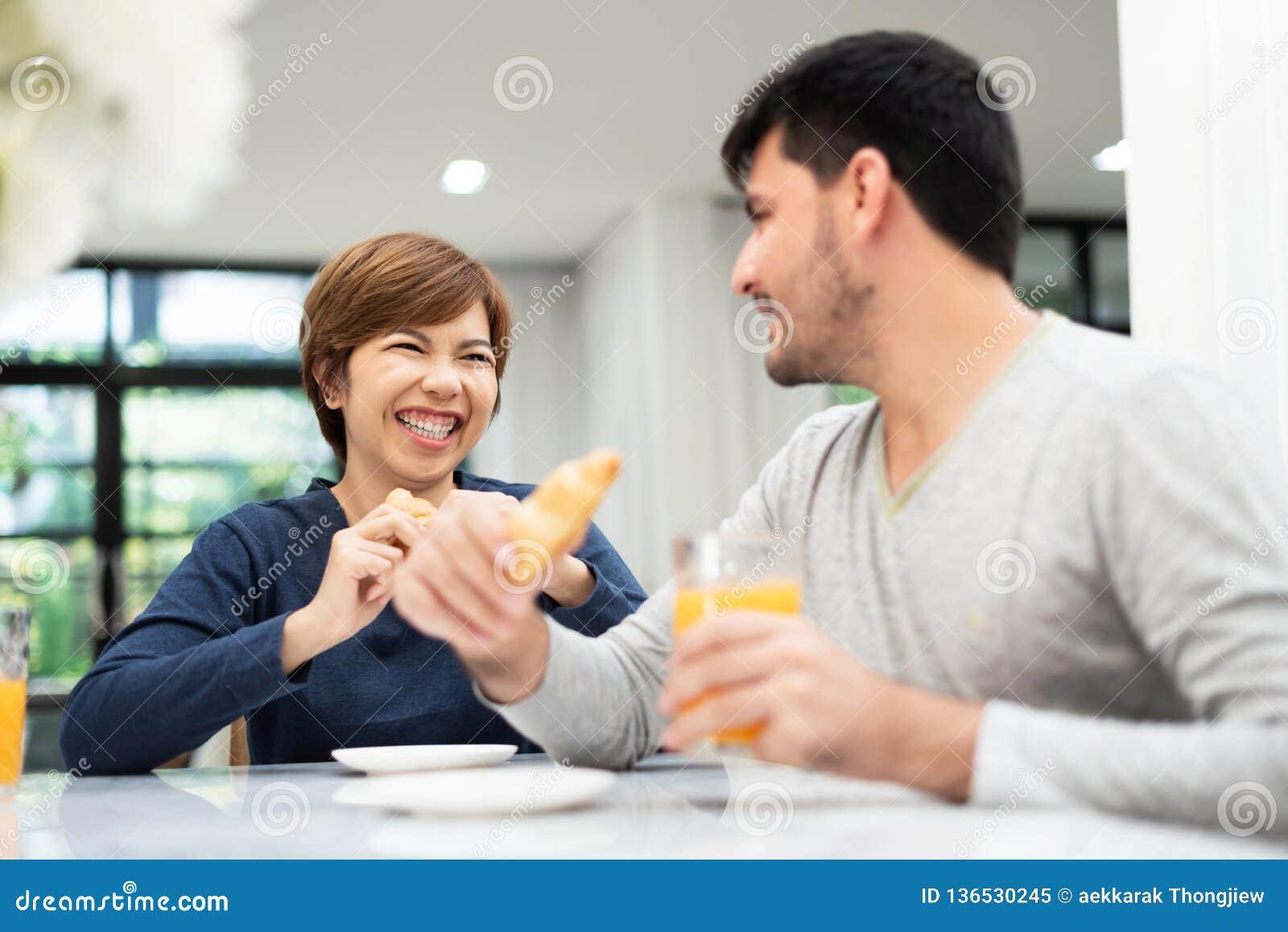 享用早餐的愉快的年轻夫妇