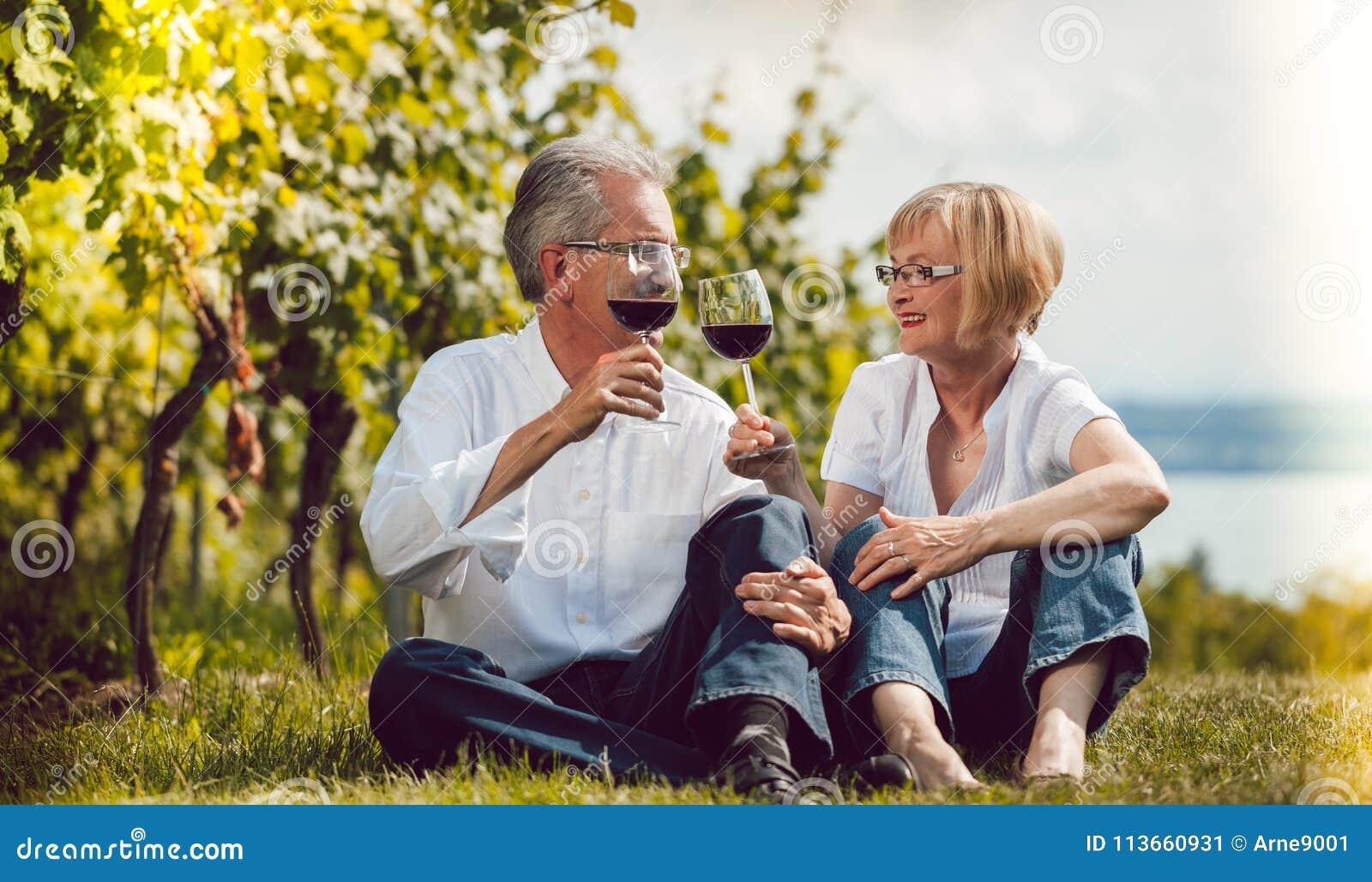 享用红葡萄酒的资深夫妇户外,妇女和人叮当响
