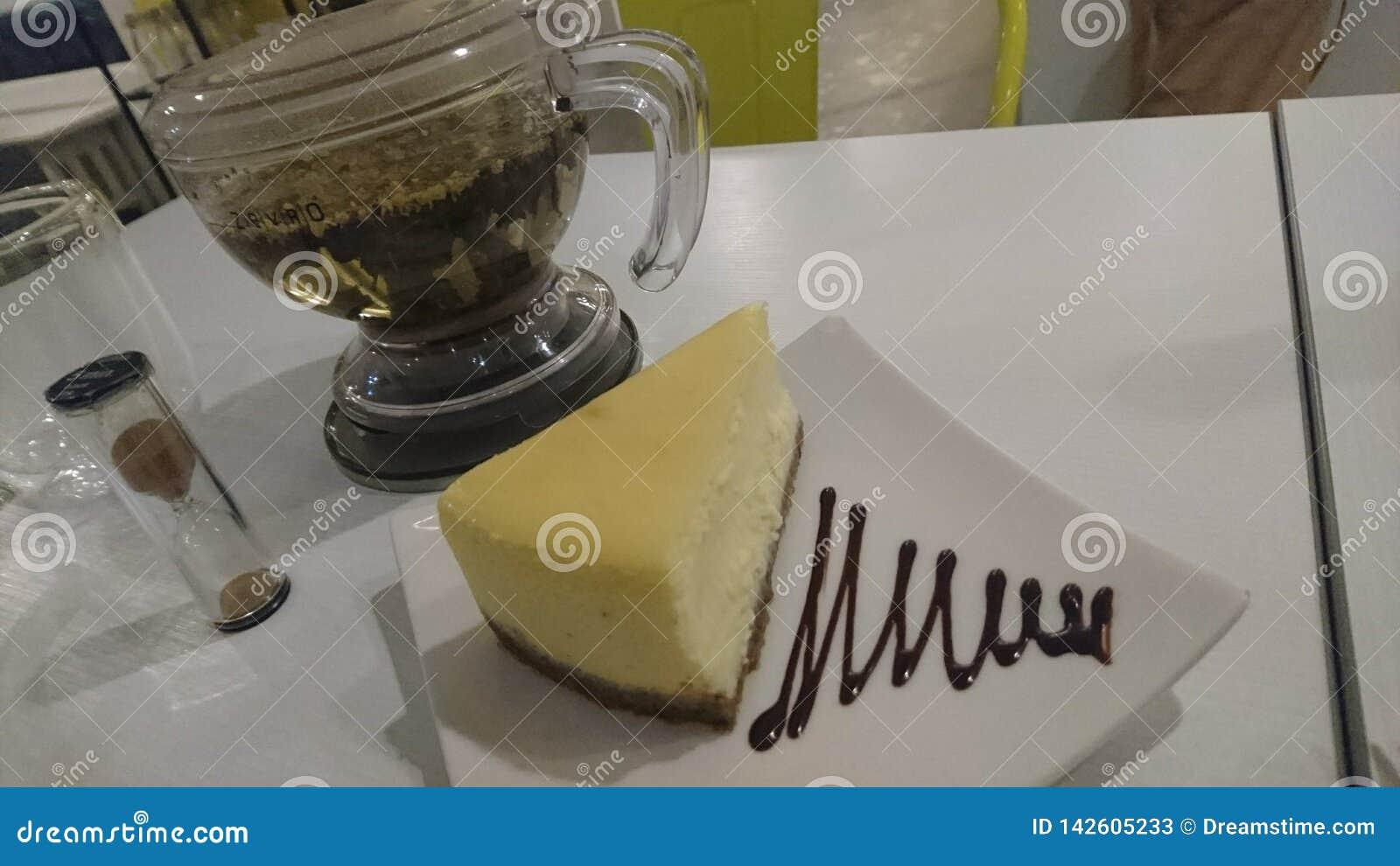 享用美味的片断乳酪蛋糕用清凉茶