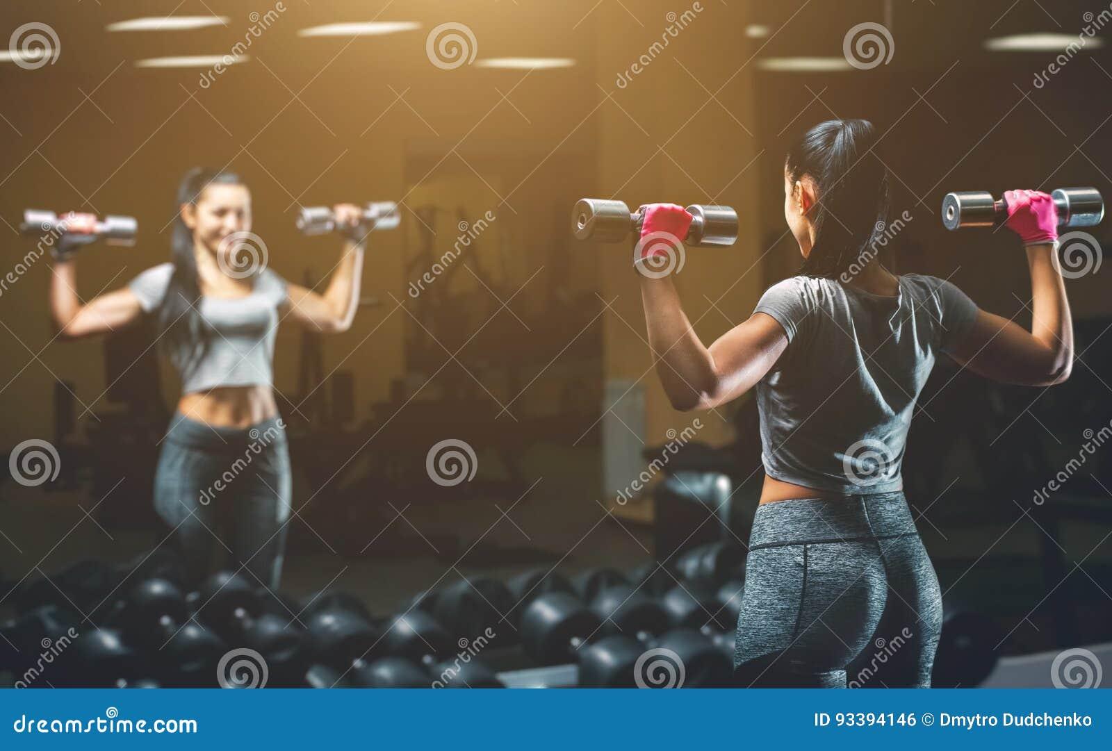 亭亭玉立,爱好健美者女孩,举站立在镜子前面的重的哑铃,当训练在健身房时