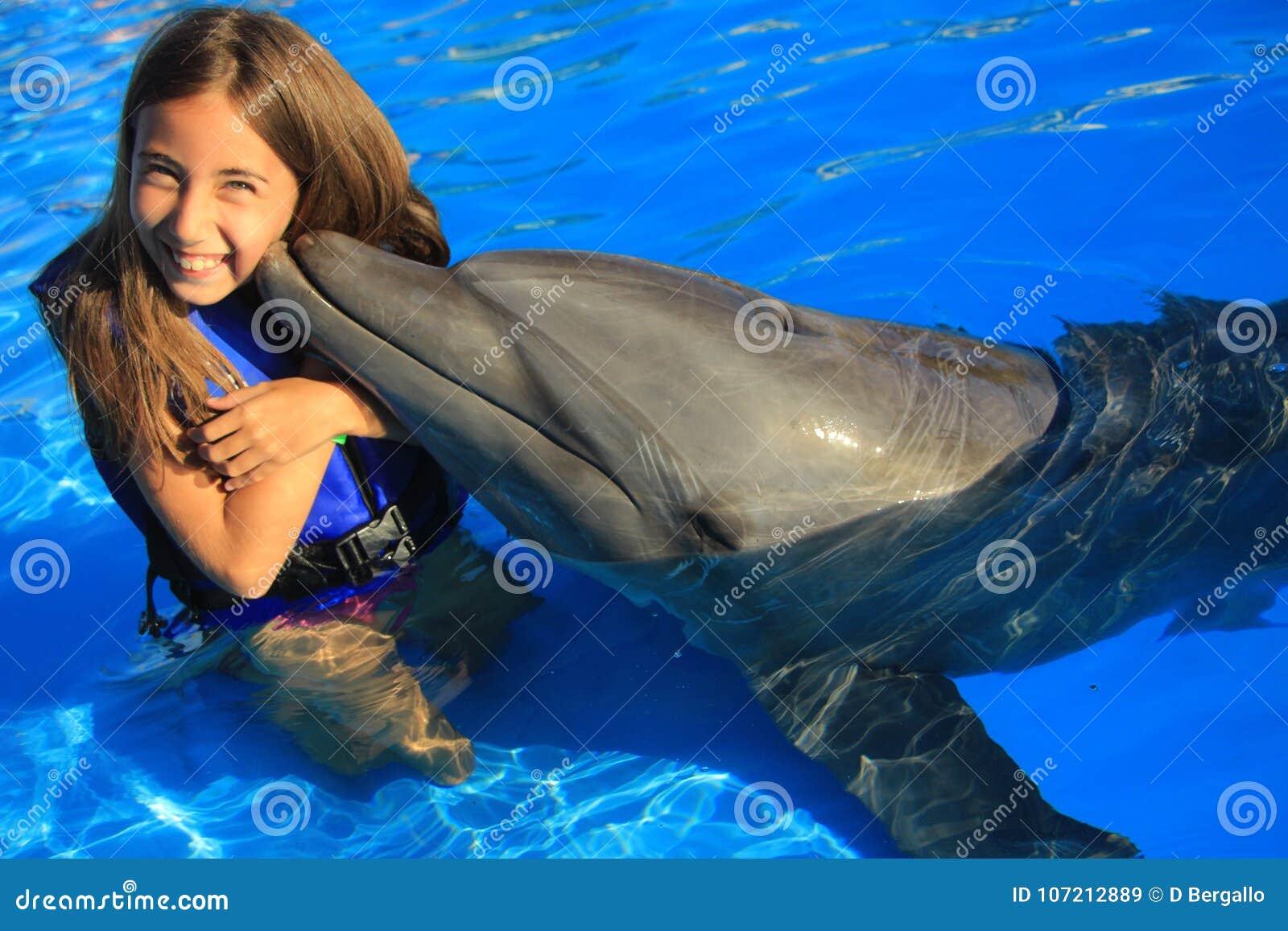 亲吻一个华美的海豚鸭脚板微笑的面孔愉快的孩子的小女孩孩子游泳瓶鼻子海豚