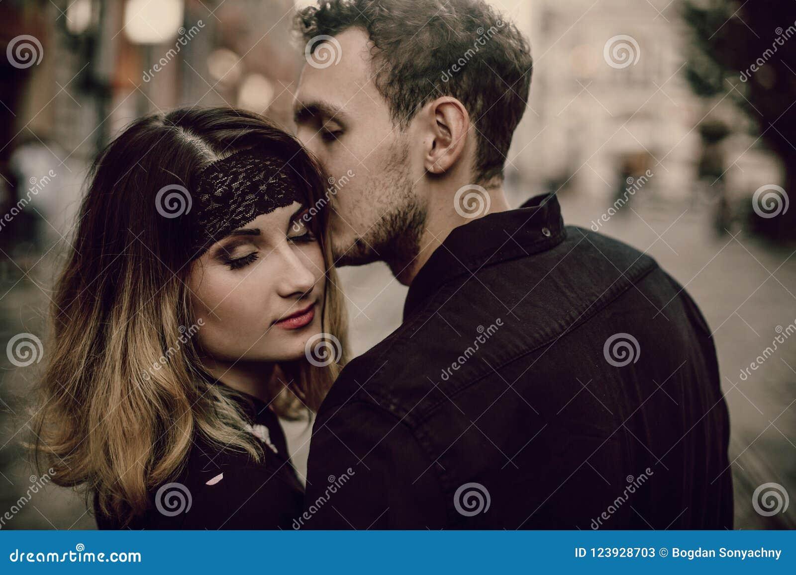 亲吻一对浪漫的夫妇的特写镜头,英俊的有胡子的人亲吻