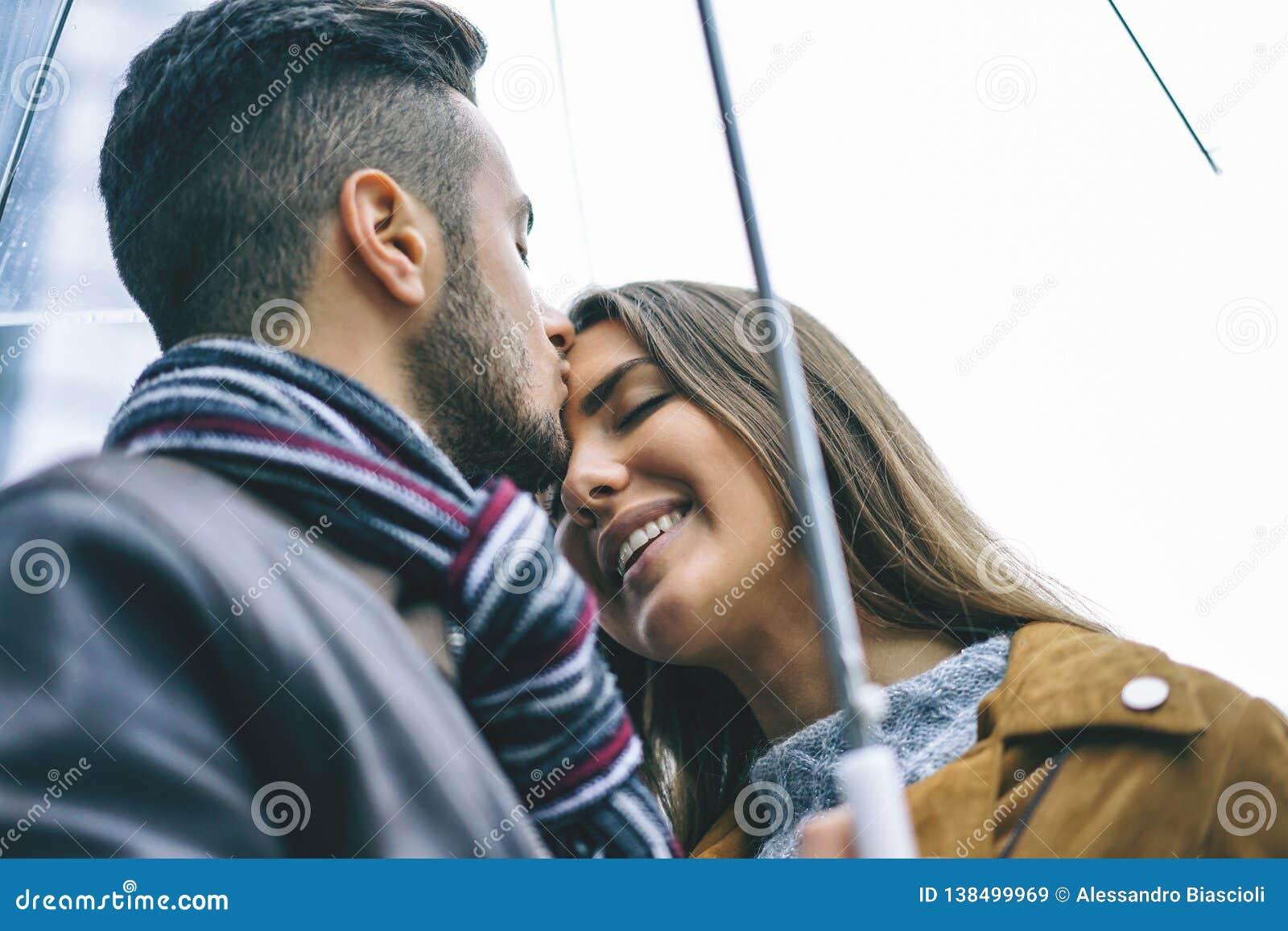 亲吻在一把伞在一下雨天-帅哥下的愉快的夫妇亲吻他的前额女朋友在雨下-爱,人们,