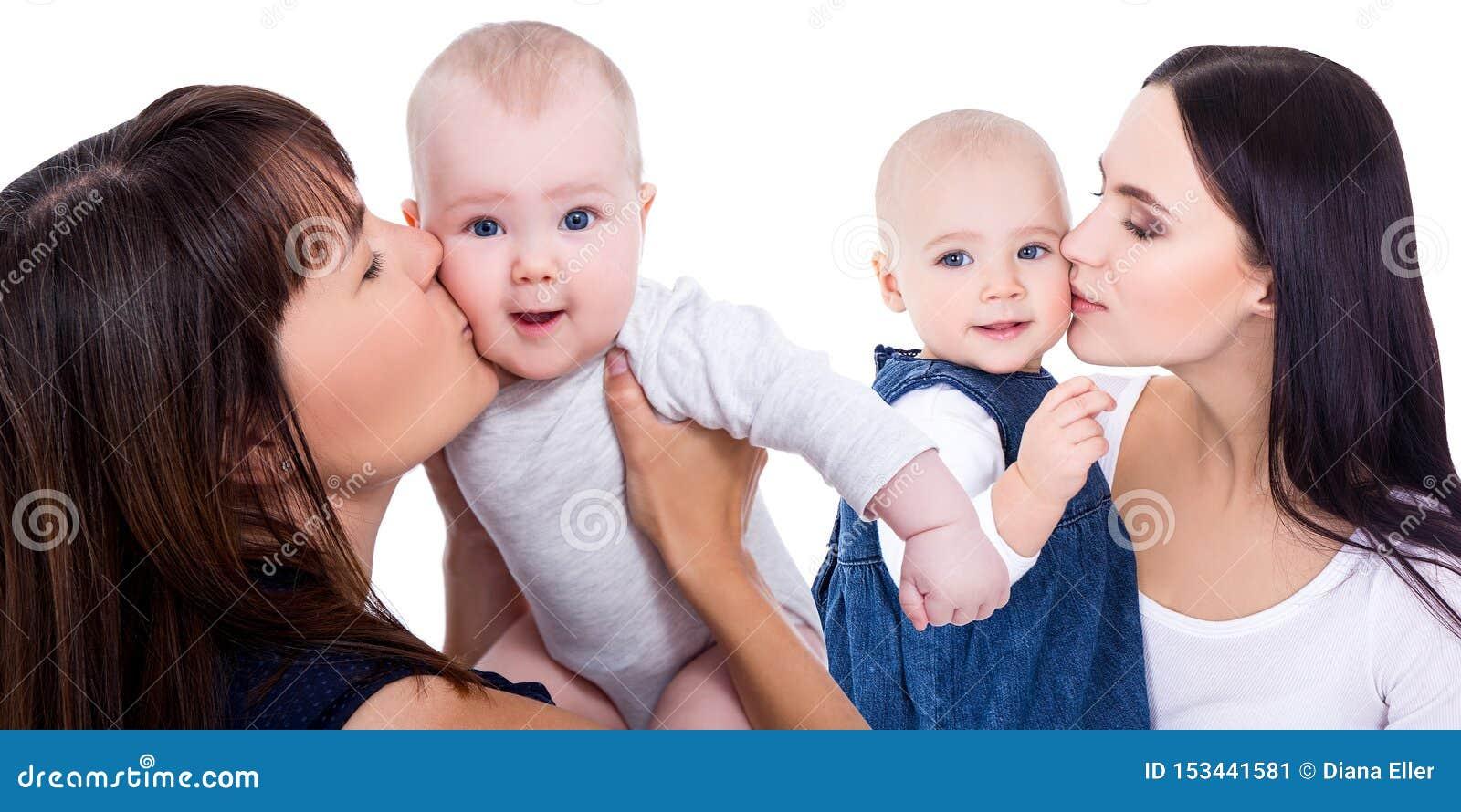 亲吻小女儿的愉快的年轻母亲画象隔绝在白色
