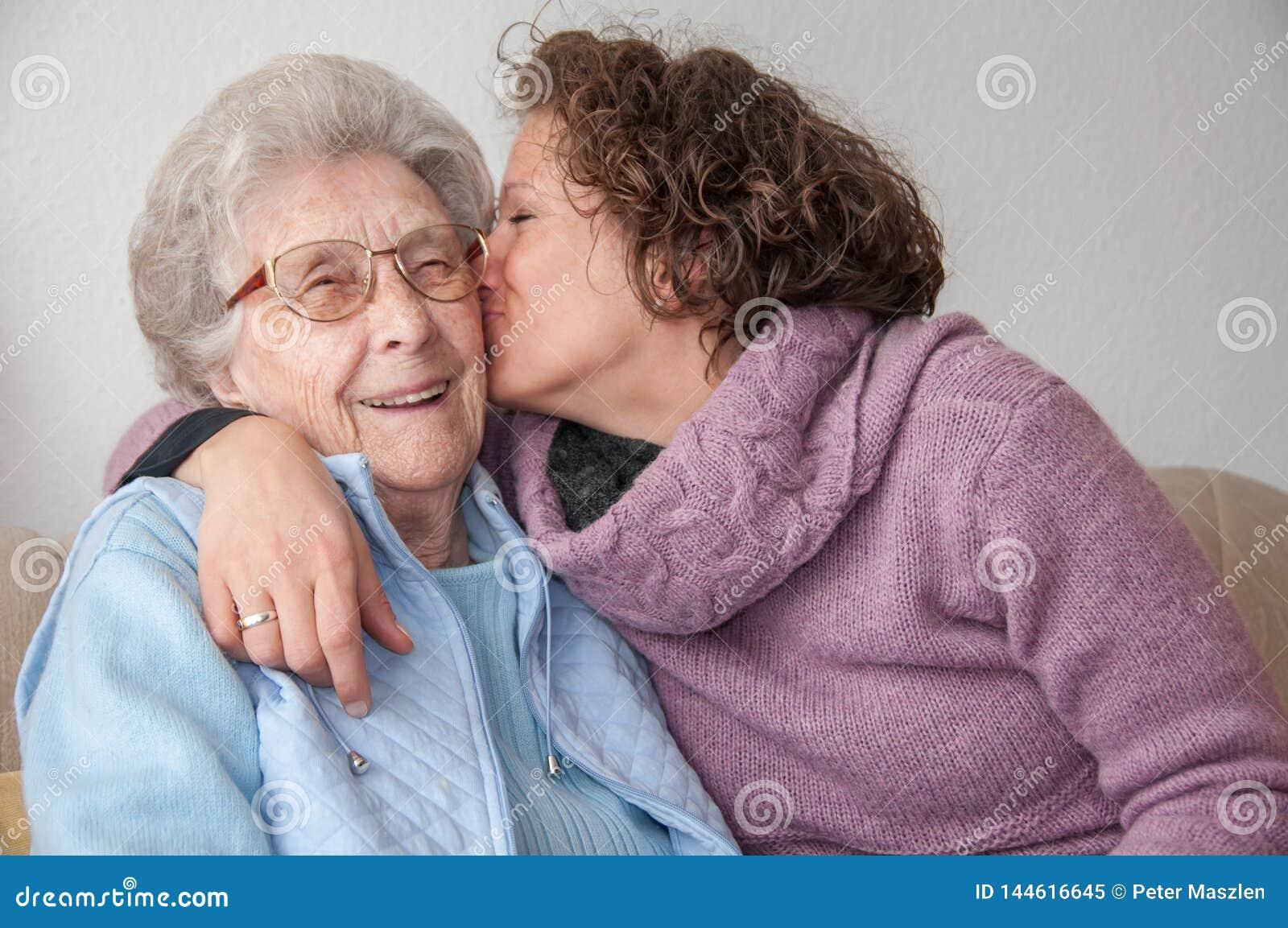 亲吻资深妇女的年轻女人
