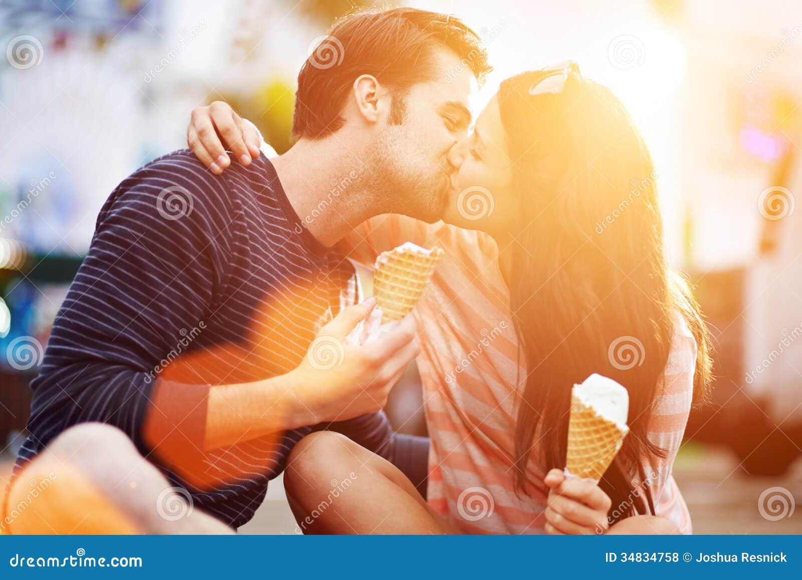 亲吻浪漫的夫妇,当拿着冰淇凌时
