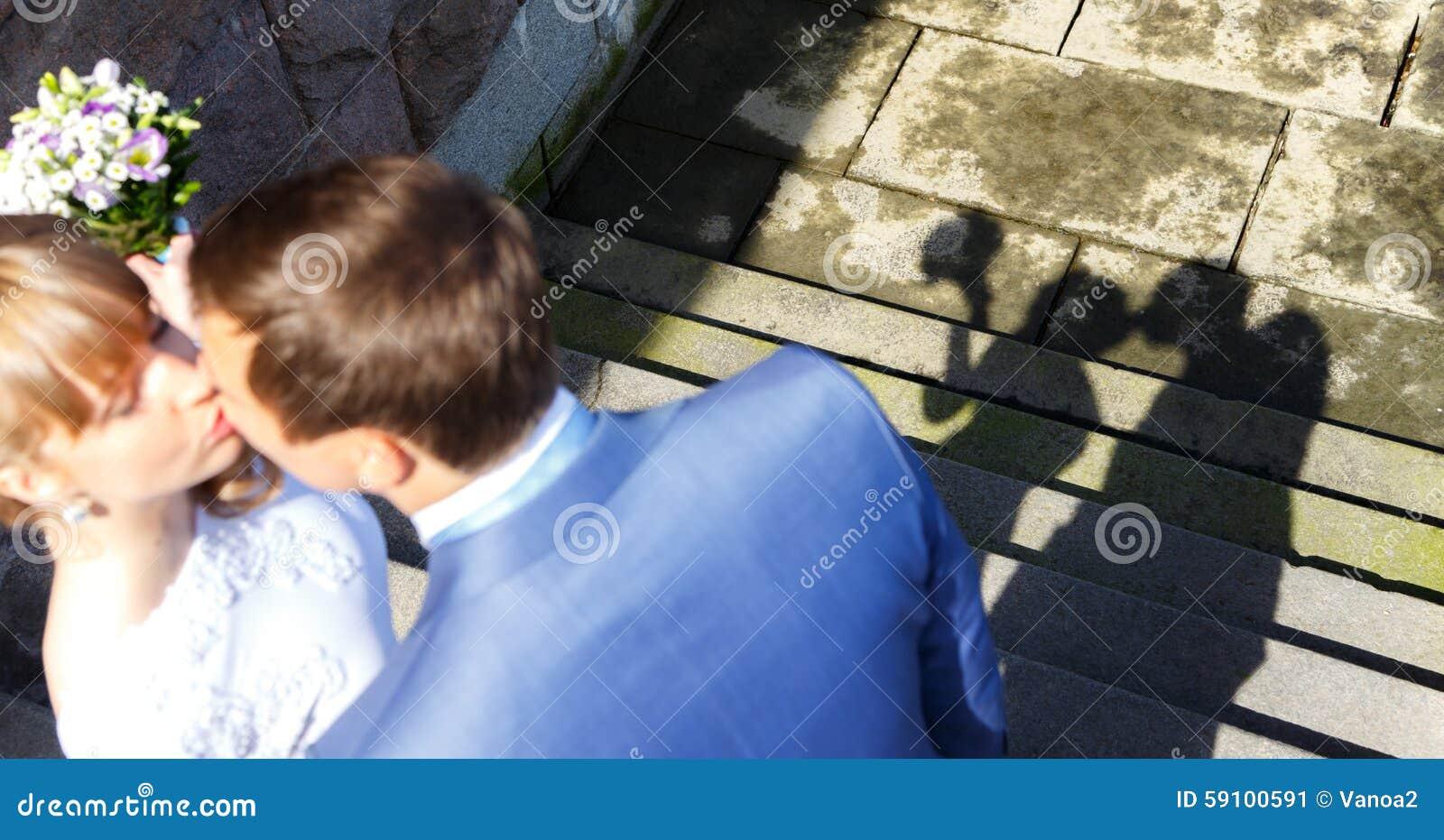 亲吻的年轻人的阴影与在石堤防的夫妇结婚