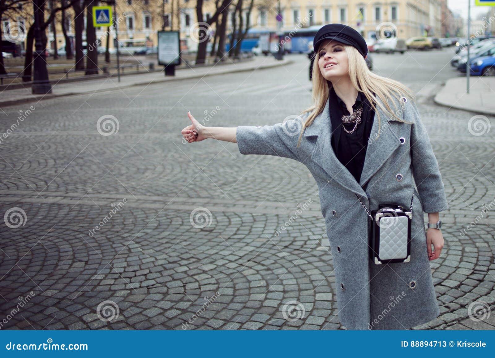 年轻人、熟悉内情和有吸引力的白肤金发的称赞的出租汽车、女孩一个时髦的帽子的和一件灰色外套