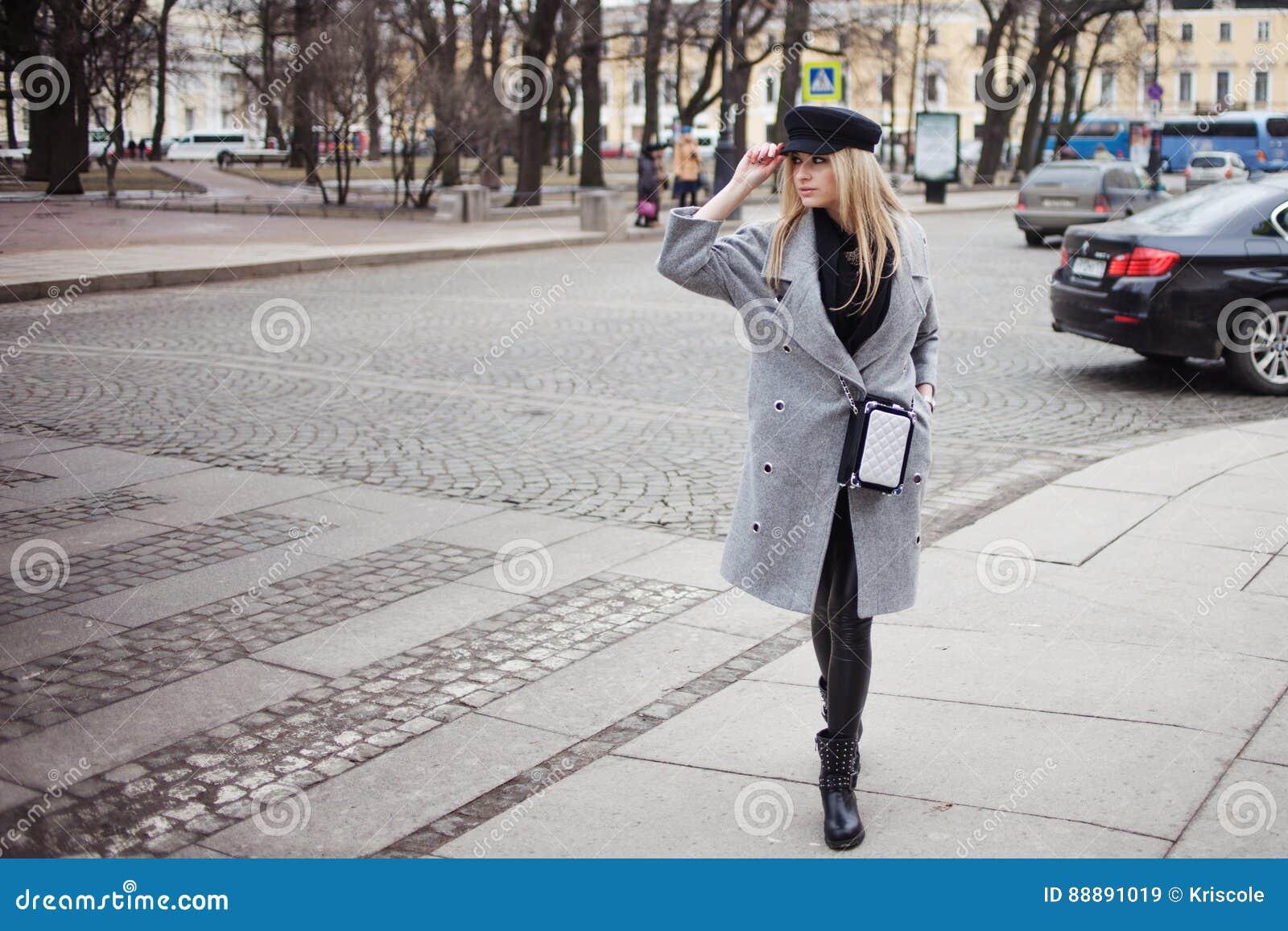年轻人、熟悉内情和有吸引力的白肤金发的身分在行人交叉路,女孩一个时髦的帽子的和一件灰色外套