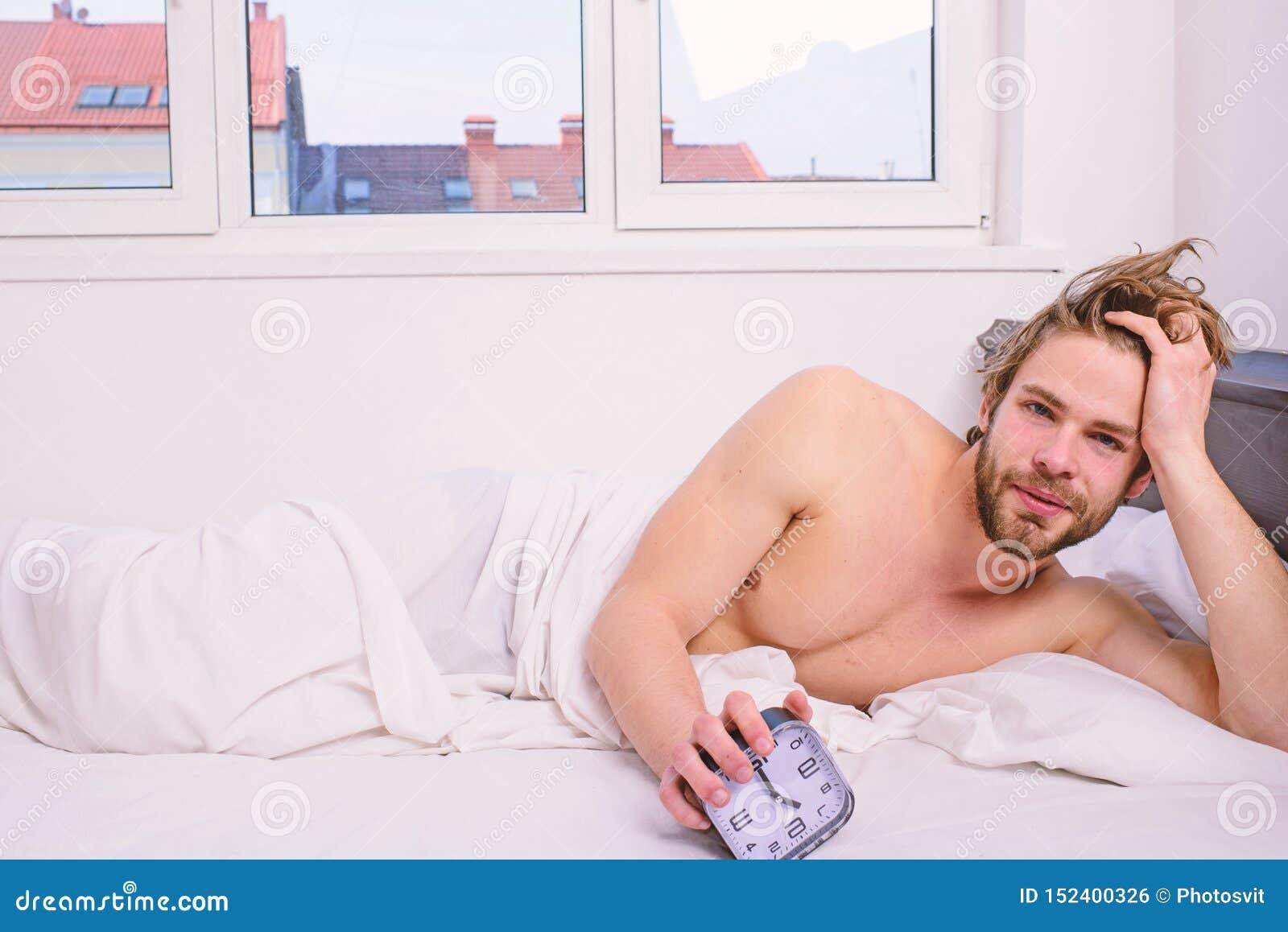 人不剃须的被放置的床举行闹钟 有人不剃须的有胡子的警惕的面孔休息棍子日程表同样上床时间苏醒