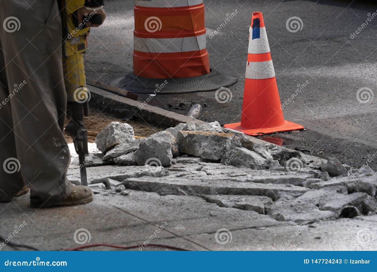 人与在路的手提凿岩机一起使用