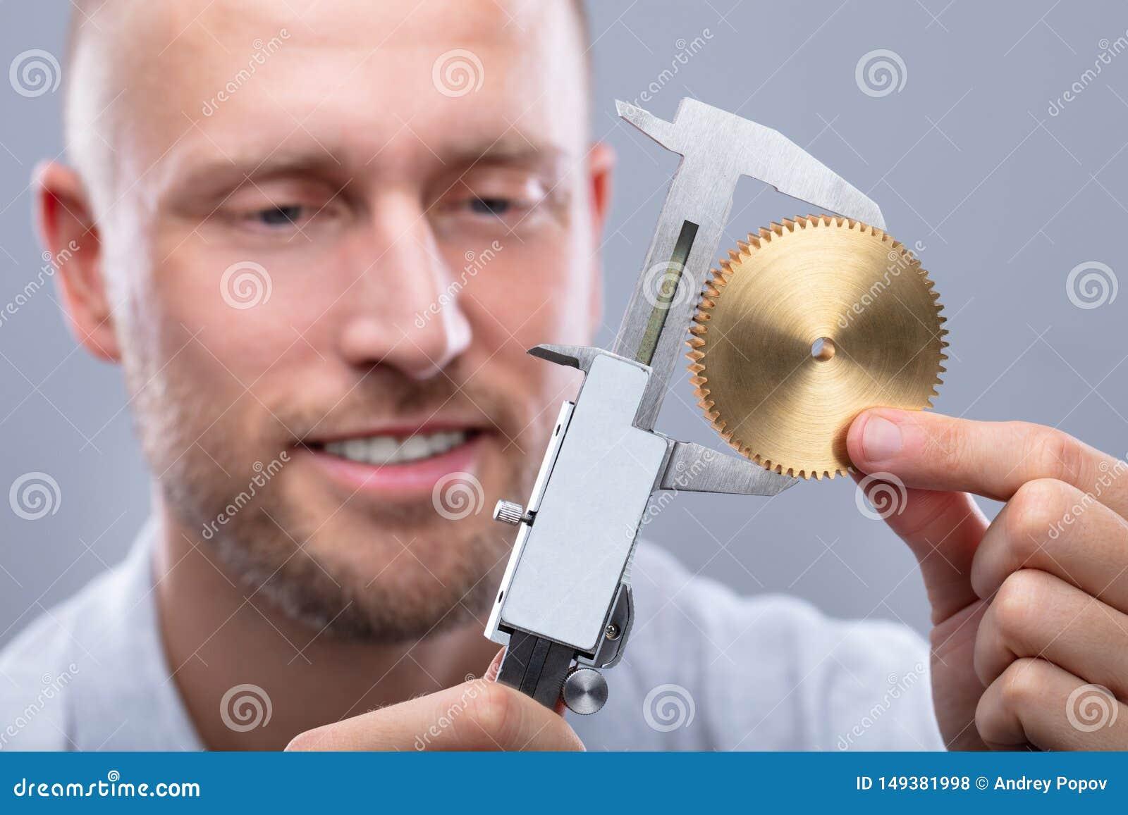 人与数字游标卡尺的测量的齿轮的大小