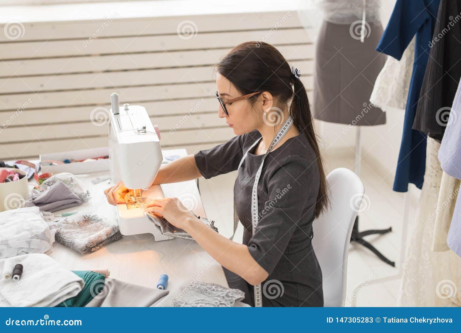 人们、裁缝和时尚概念-时尚编辑侧视图画象玻璃的使用缝纫机