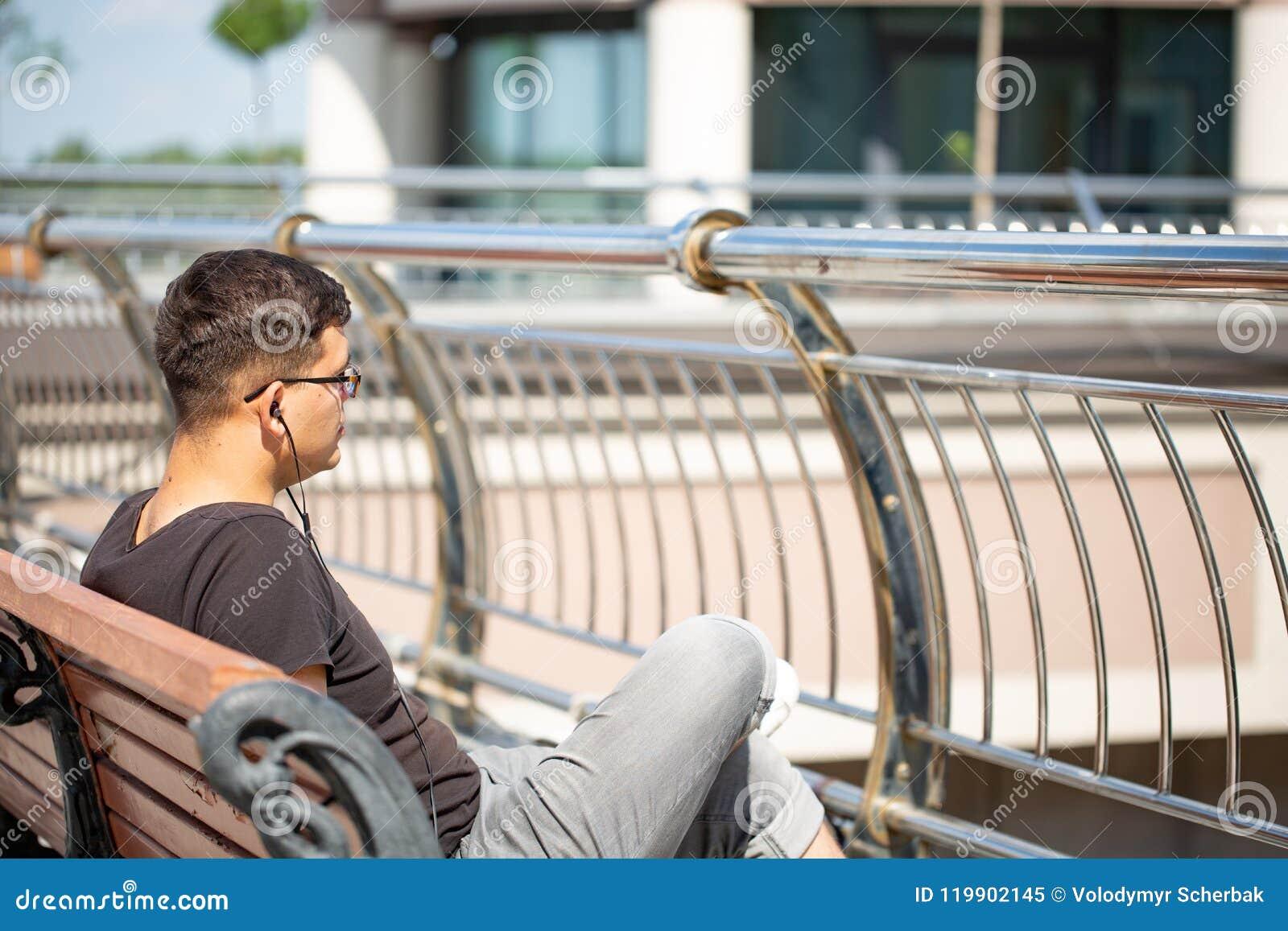 人们、音乐、技术、休闲和生活方式-有耳机的行家人听到在城市街道长凳的音乐的