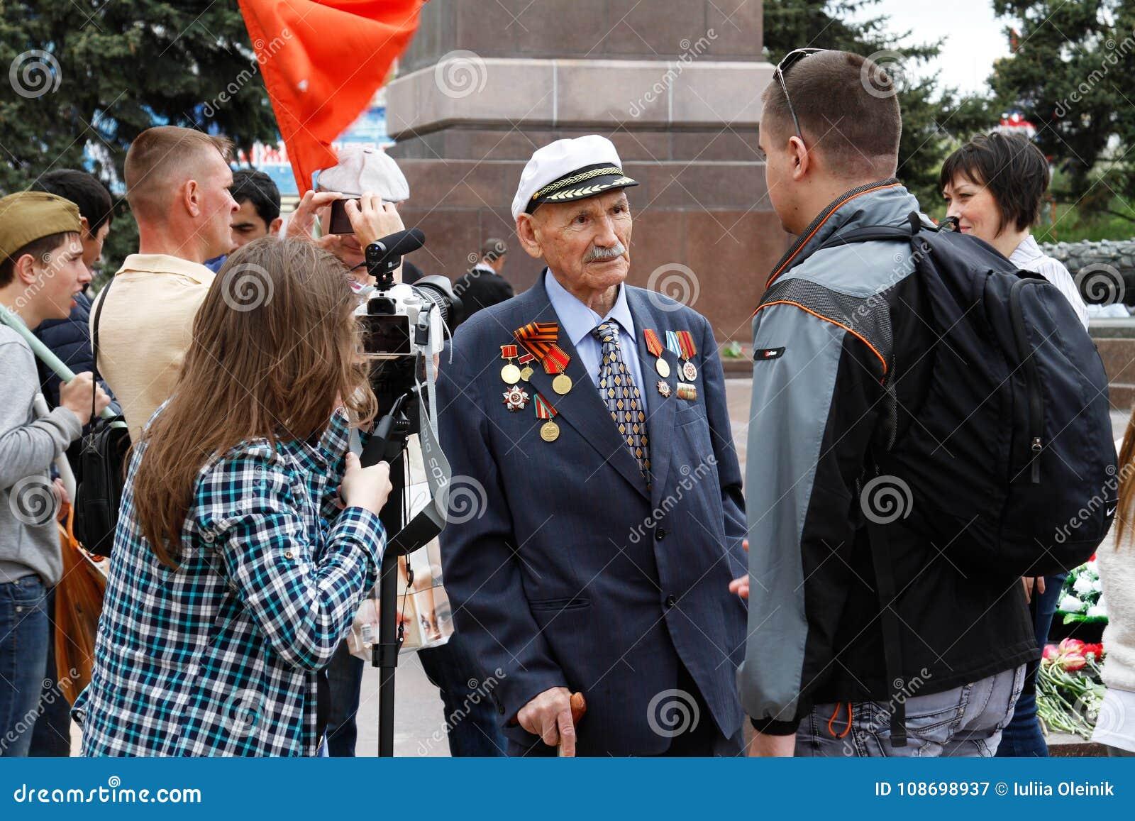 人们在伏尔加格勒采访第二次世界大战的退伍军人在下落的战斗机的正方形的