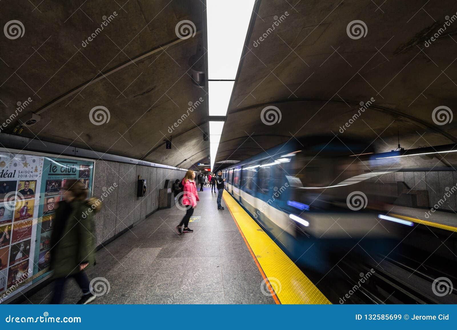 人们在彻特des Neiges驻地平台,蓝线的等待一个地铁,而地铁火车来临,与速度迷离