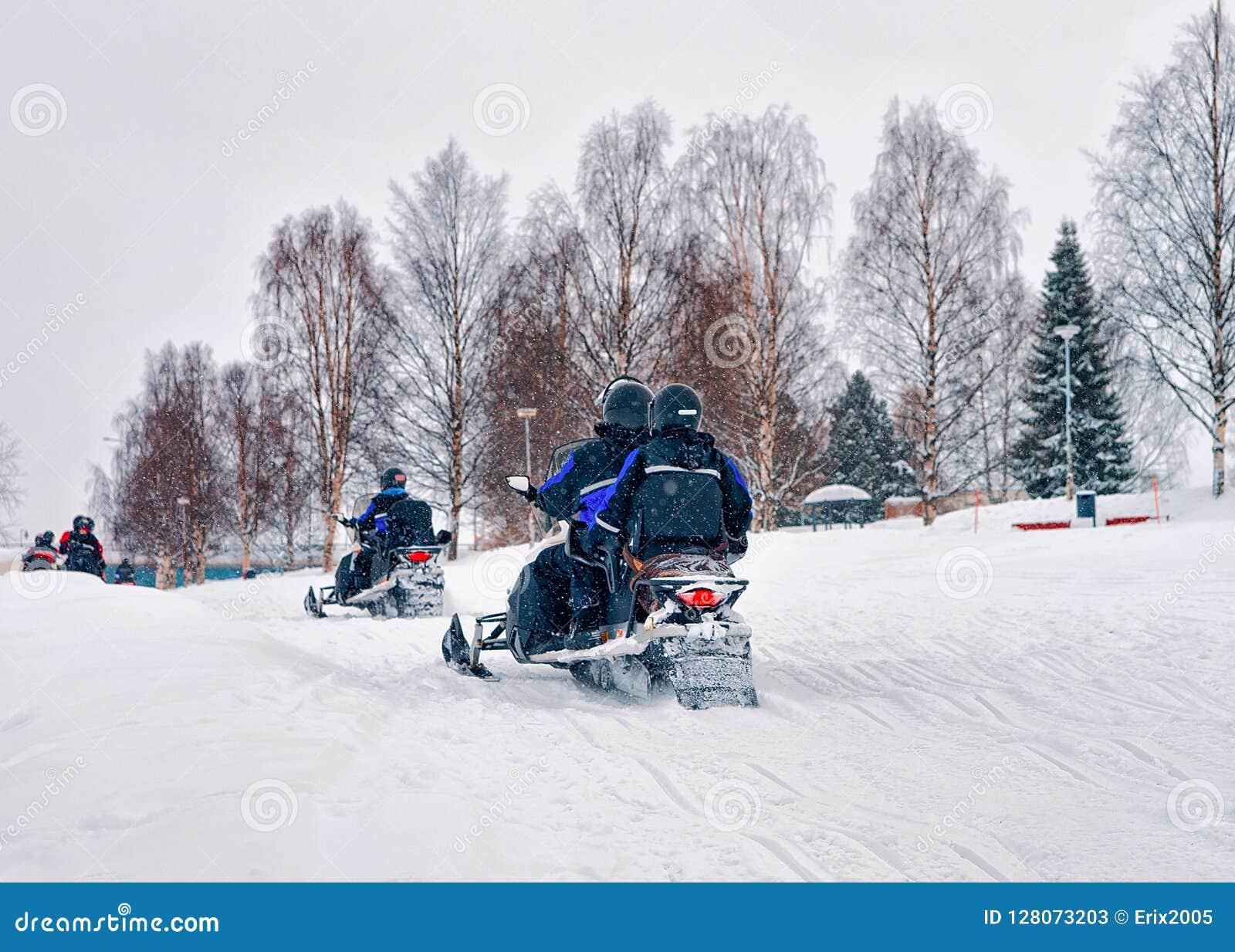 人们在雪机动性冬天在圣诞节期间的芬兰拉普兰