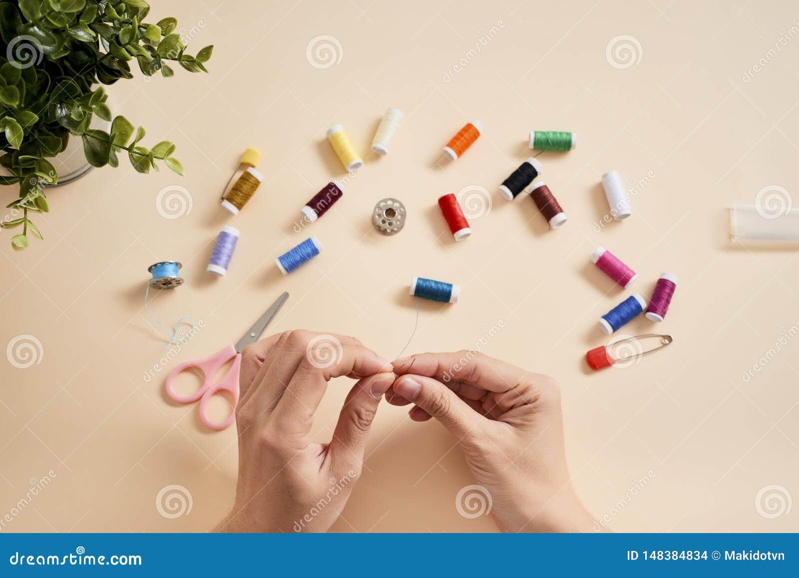 人们,针线,缝合和剪裁概念-有螺纹的裁缝妇女在针缝的织品 缝合与针的手