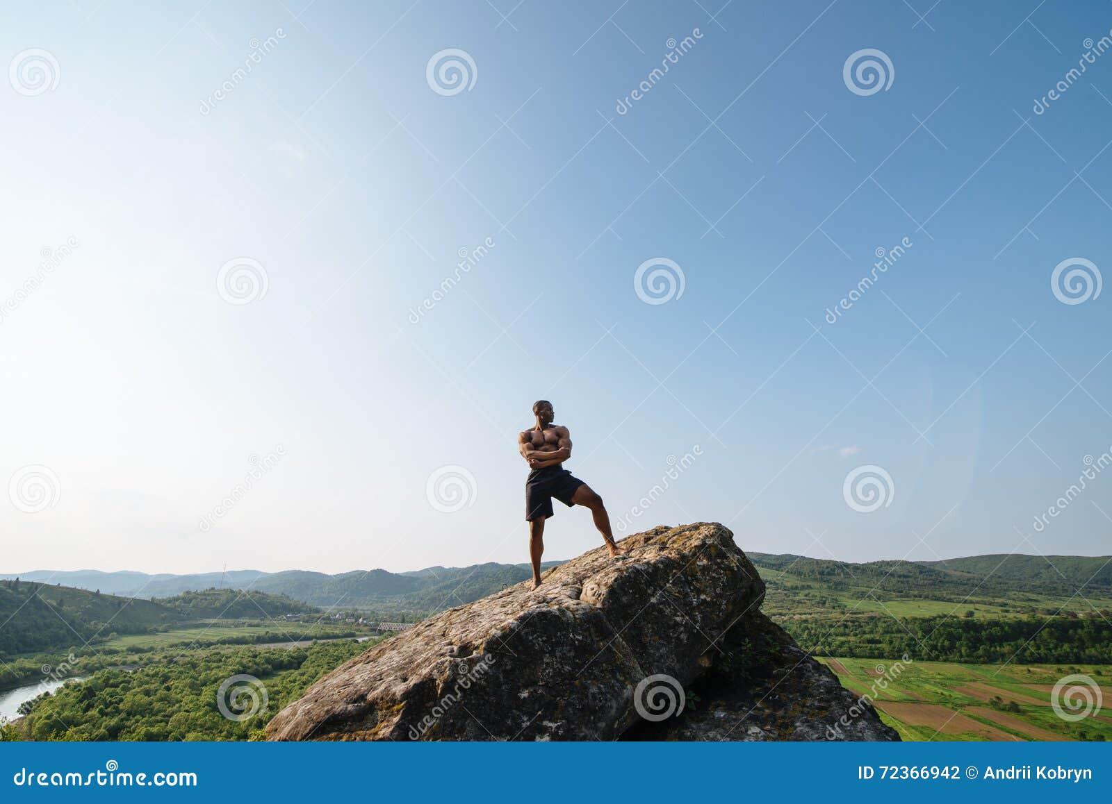 人体的完美 摆在岩石的英俊的黑人爱好健美者反对蓝天
