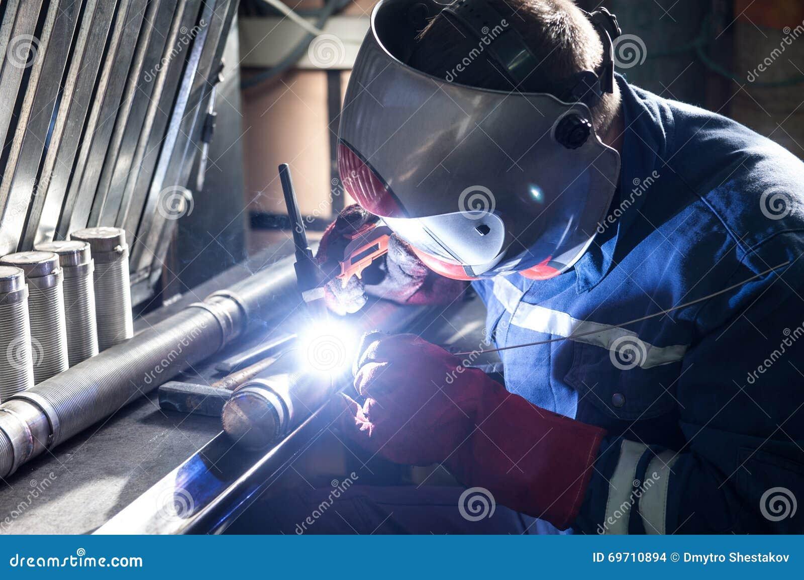人佩带的面具焊接特写镜头在车间