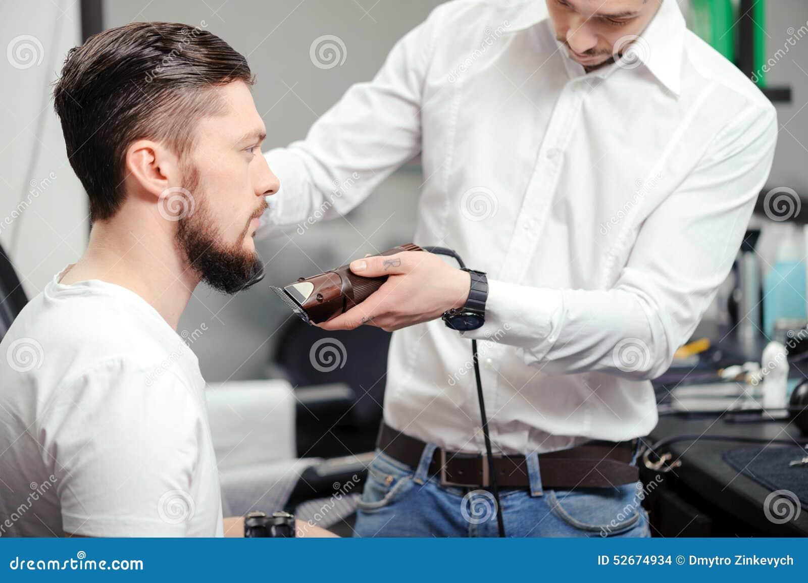 人刮他的与头发剪刀的胡子