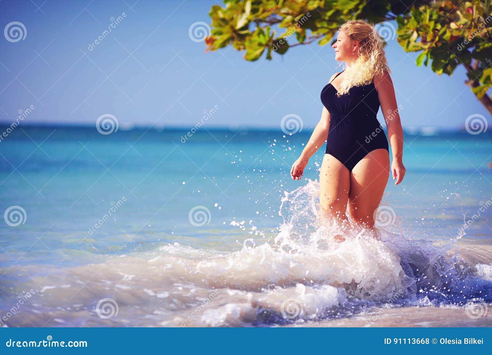 年轻人加上游泳衣的大小妇女享受在水飞溅的假期在海滩