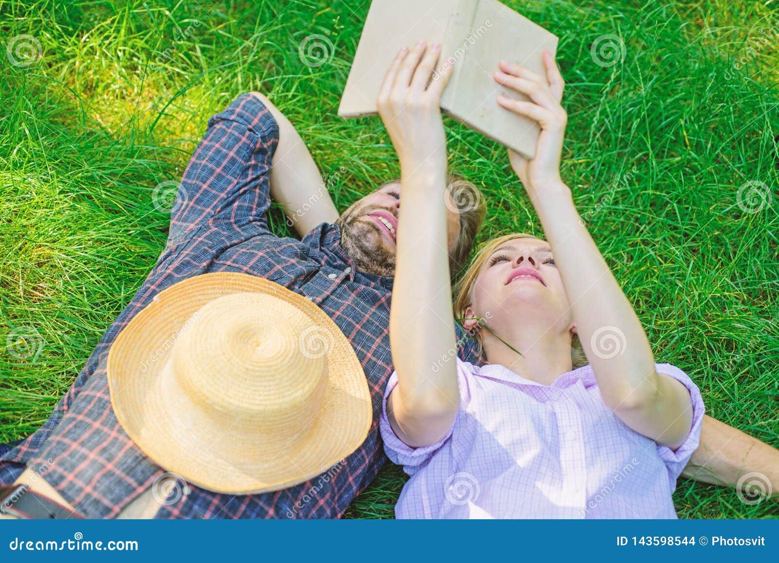 人和女孩在获得的草放置乐趣 在爱的夫妇花费休闲阅读书 夫妇知己在浪漫日期