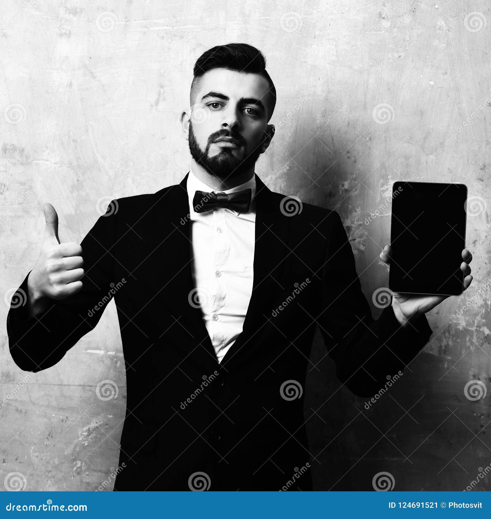 人喜欢片剂 年轻有胡子的报告人提出新的口袋设备并且显示赞许 老破裂的米黄背景