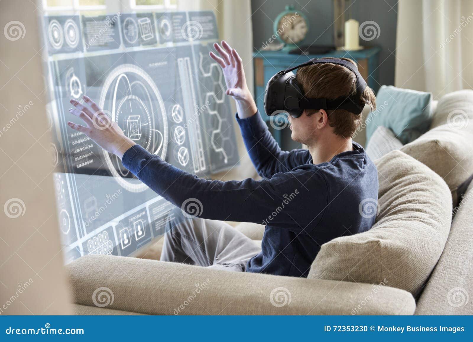 人在家坐佩带虚拟现实耳机的沙发