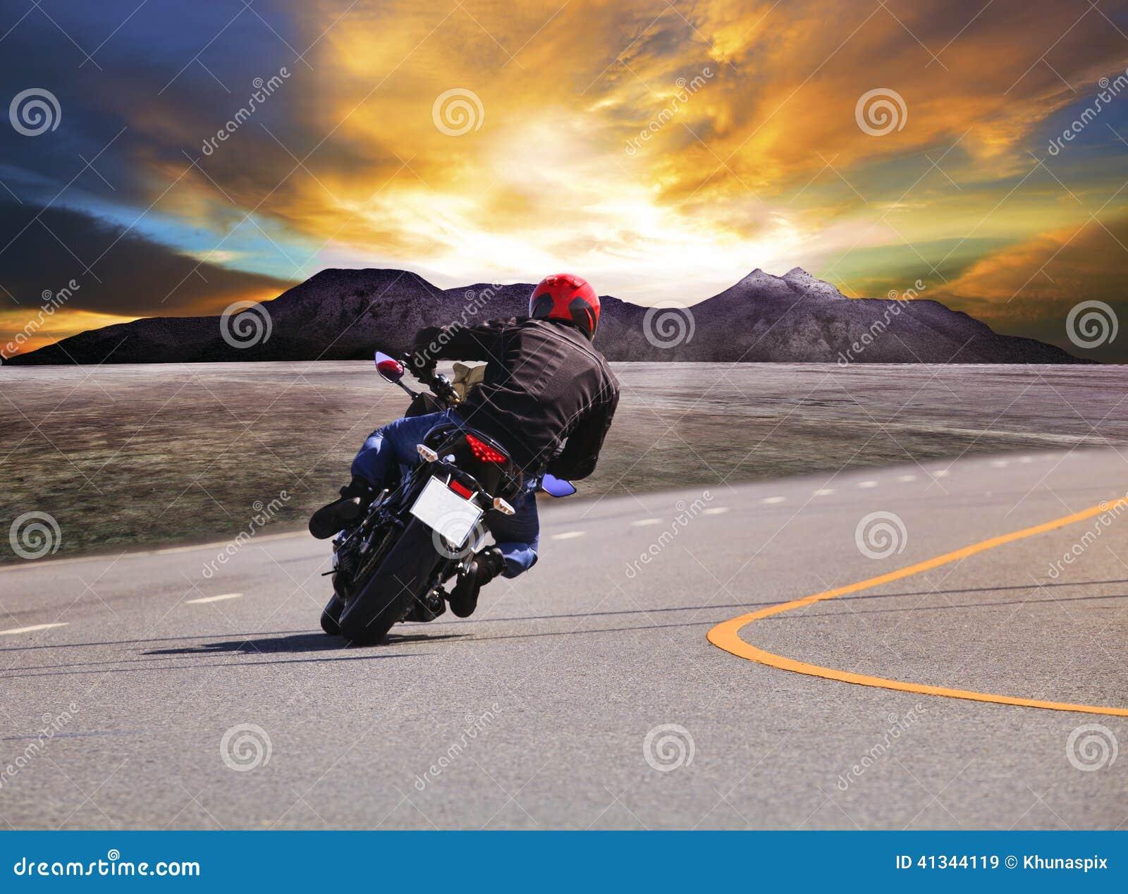 年轻人在柏油路曲线w的骑马摩托车背面图