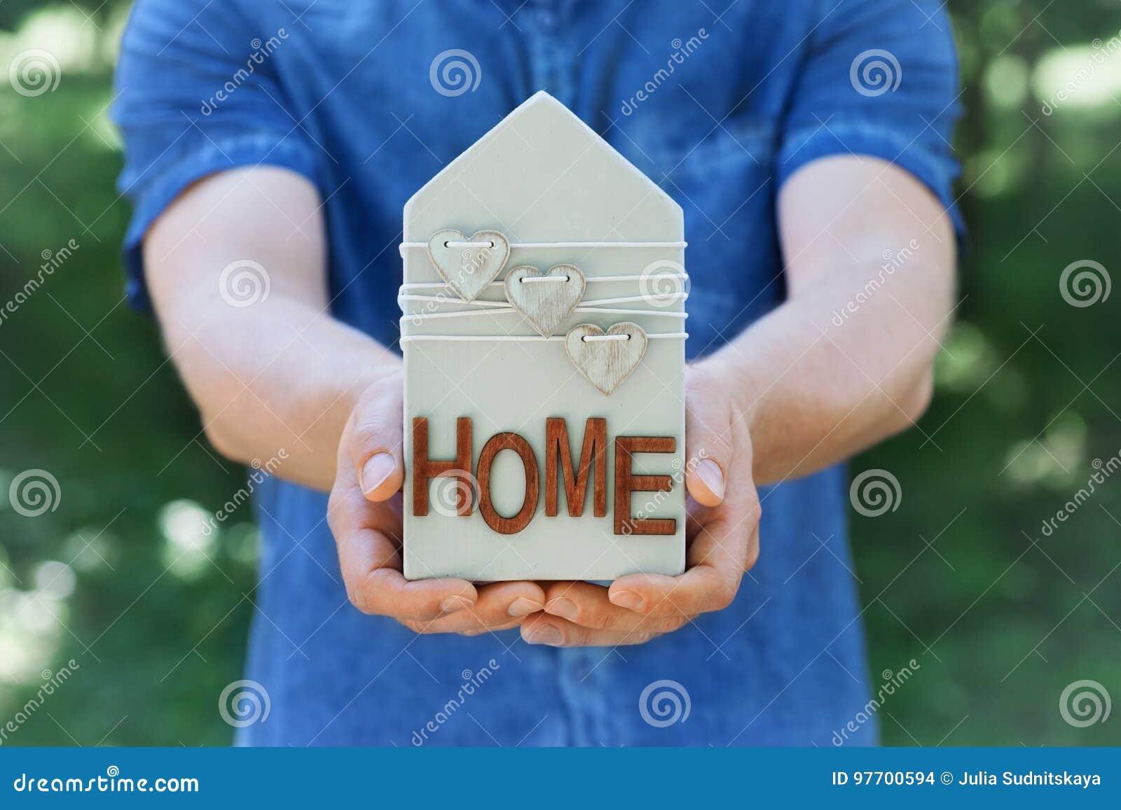 人在他的在绿色自然背景的手木房子装饰的心脏举行 房地产、保险,销售或者买一个新的家