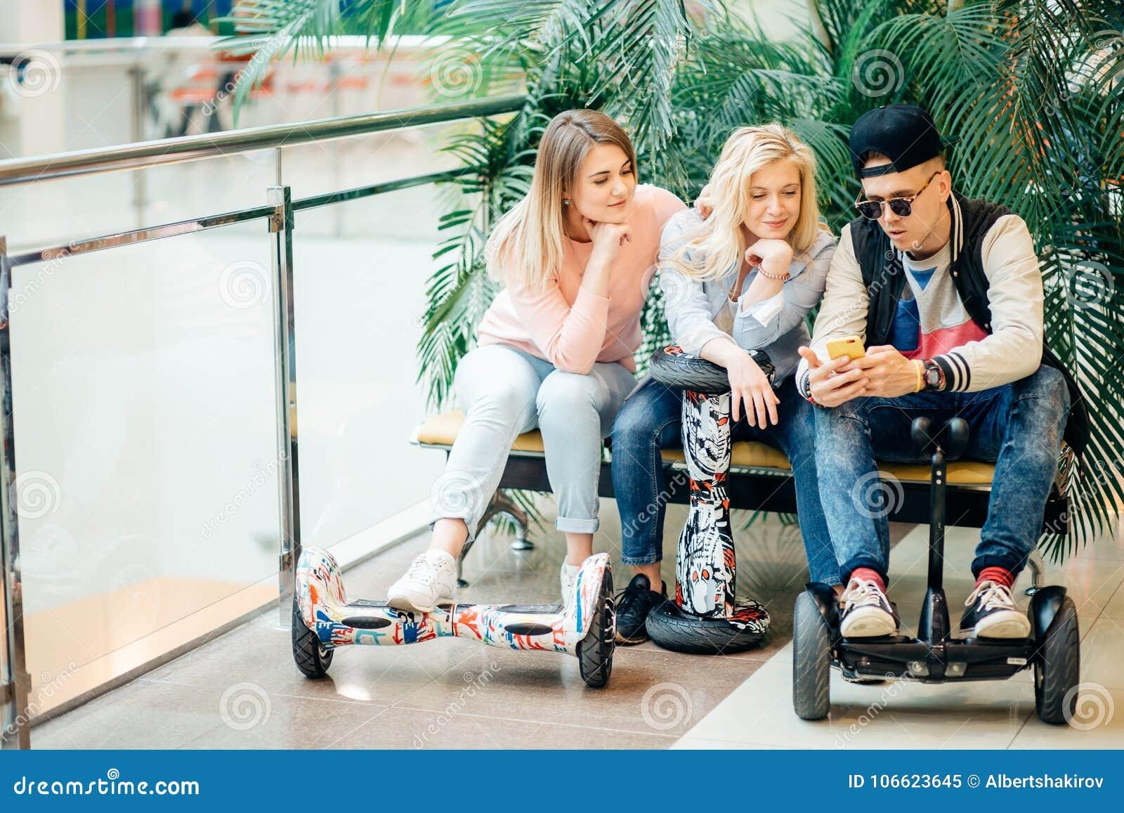 人坐在长凳和使用电话的电滑行车hoverboard的