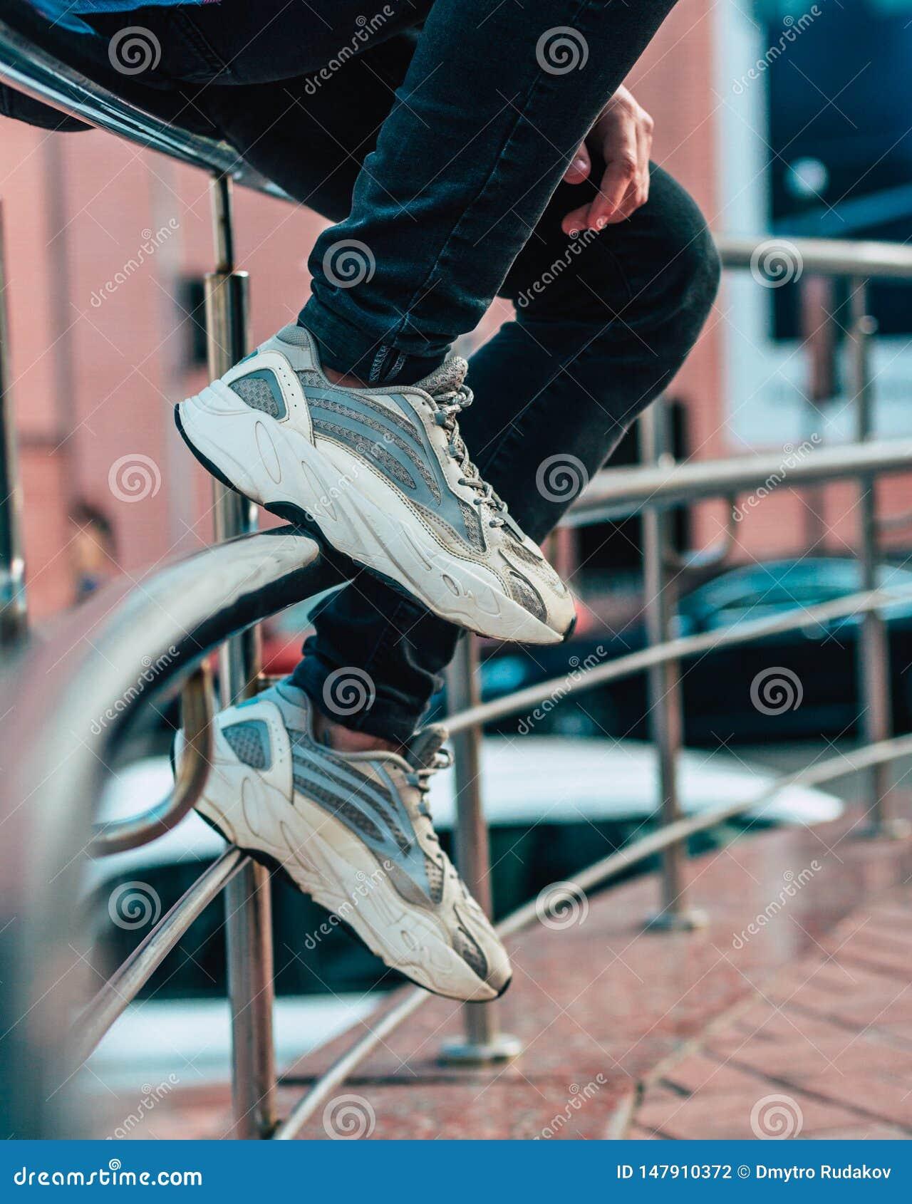 人坐篱芭佩带的牛仔裤和鹿皮鞋