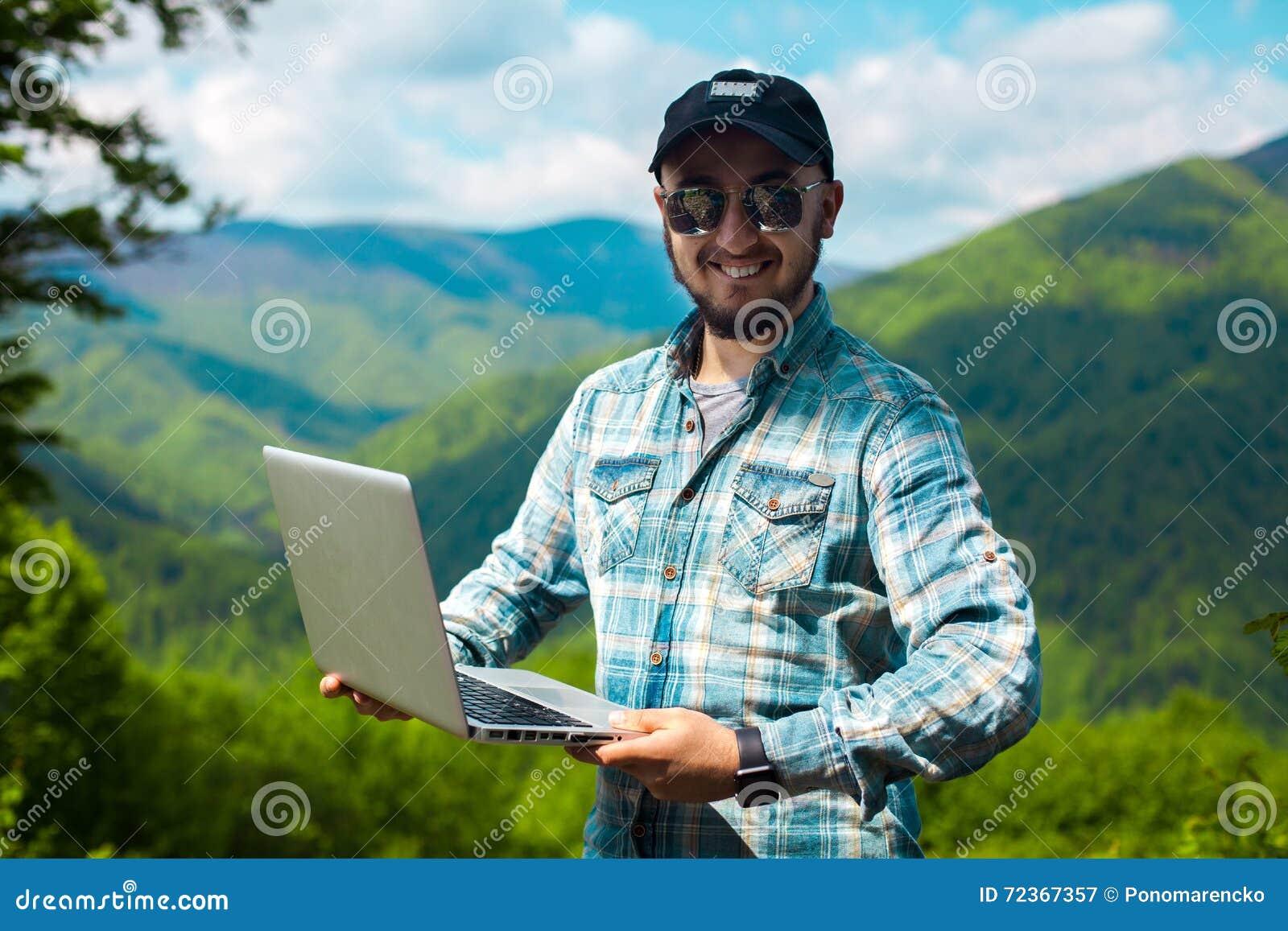 人太阳镜的和有一台膝上型计算机的在手上