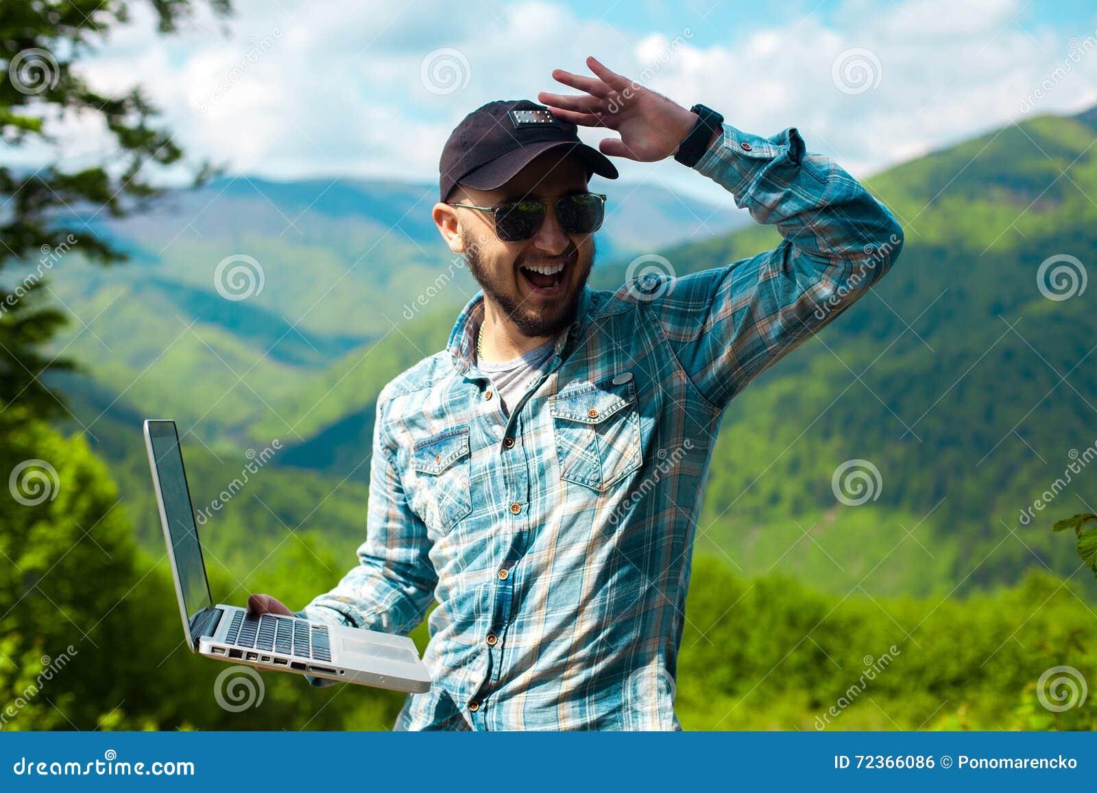 年轻人太阳镜的和有膝上型计算机的在手中