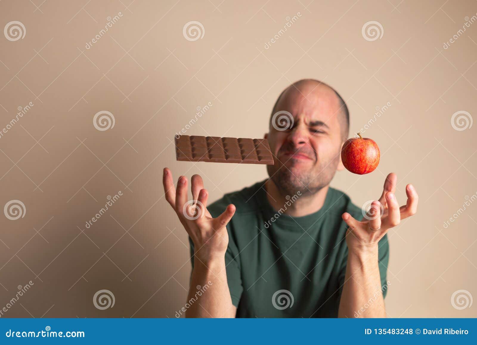 人安置在巧克力块下的一只手和其他在苹果下