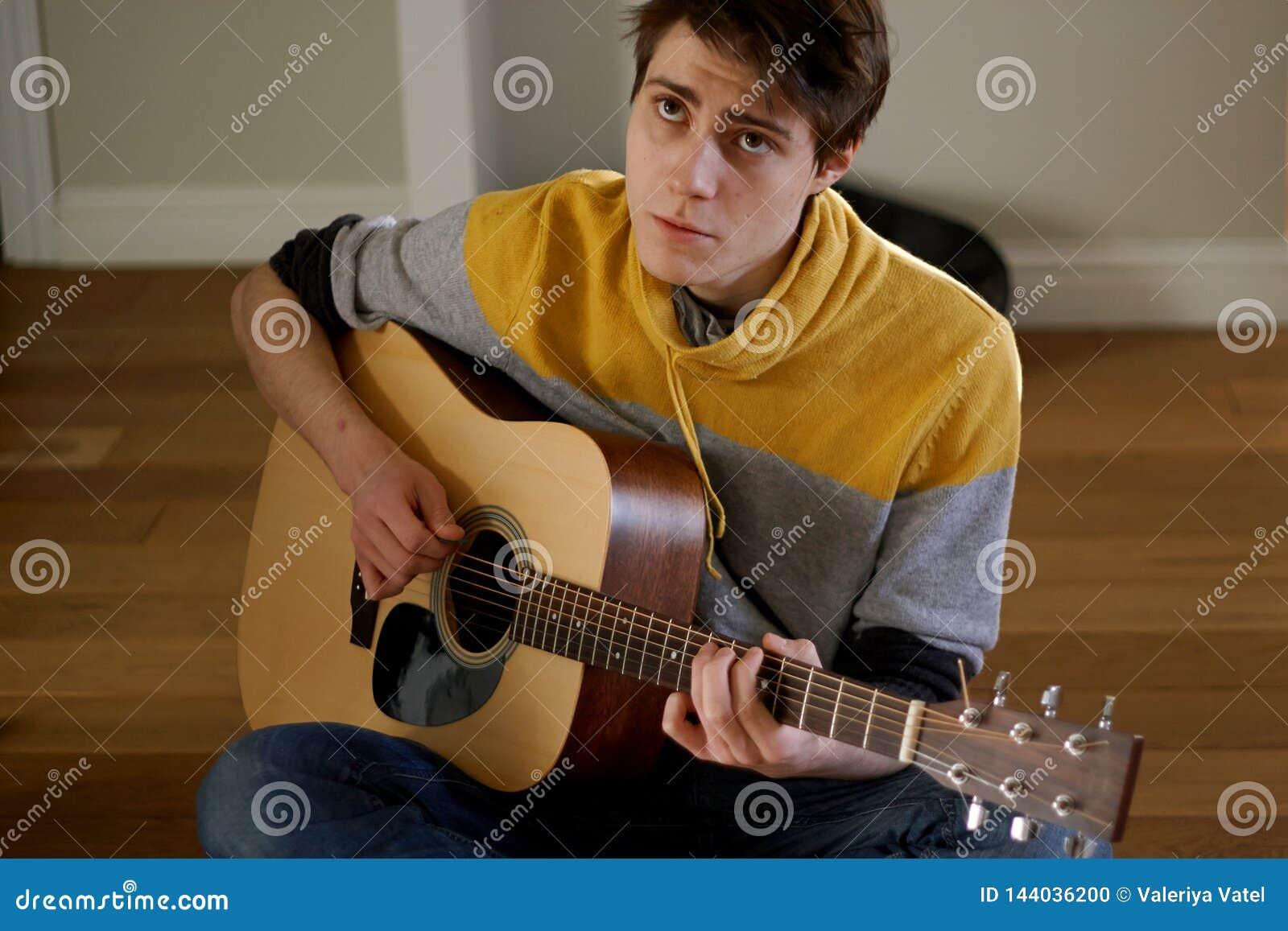 人弹吉他并且唱一首哀伤的歌曲