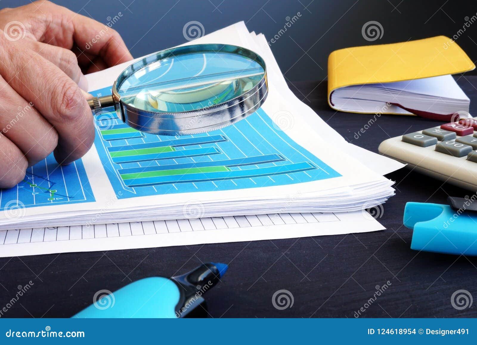 人拿着在商业文件上的放大镜与财政统计 被验核