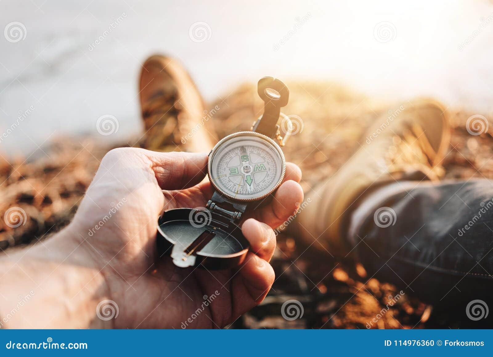 人旅客举行指南针在手中在远足起动的背景腿 被弄脏的背景