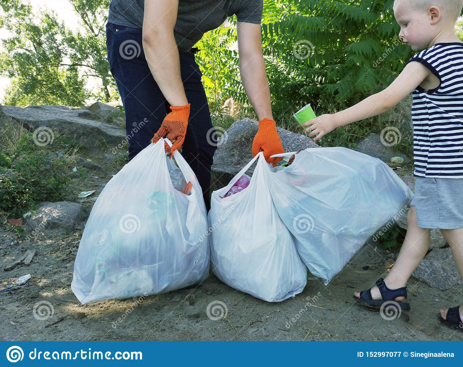 人清除了公园和海滩从残骸 他拿着袋子垃圾和塑料 教的孩子的概念