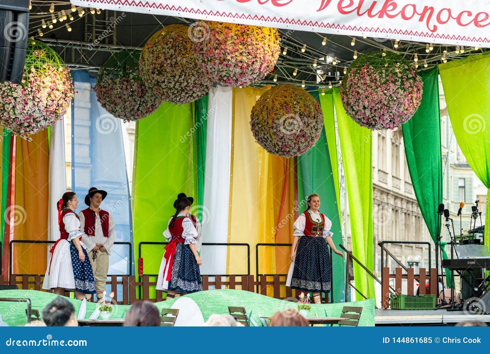 人群在阶段观看小学生执行在Pragues复活节市场庆祝期间在老城广场