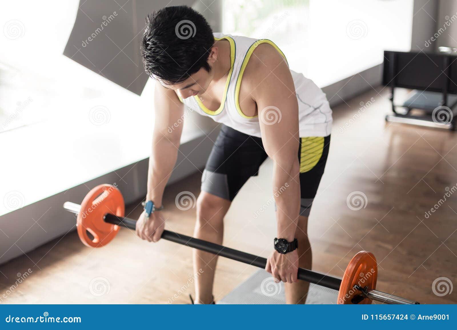 人行使弯曲了在与杠铃的划船背部肌肉的