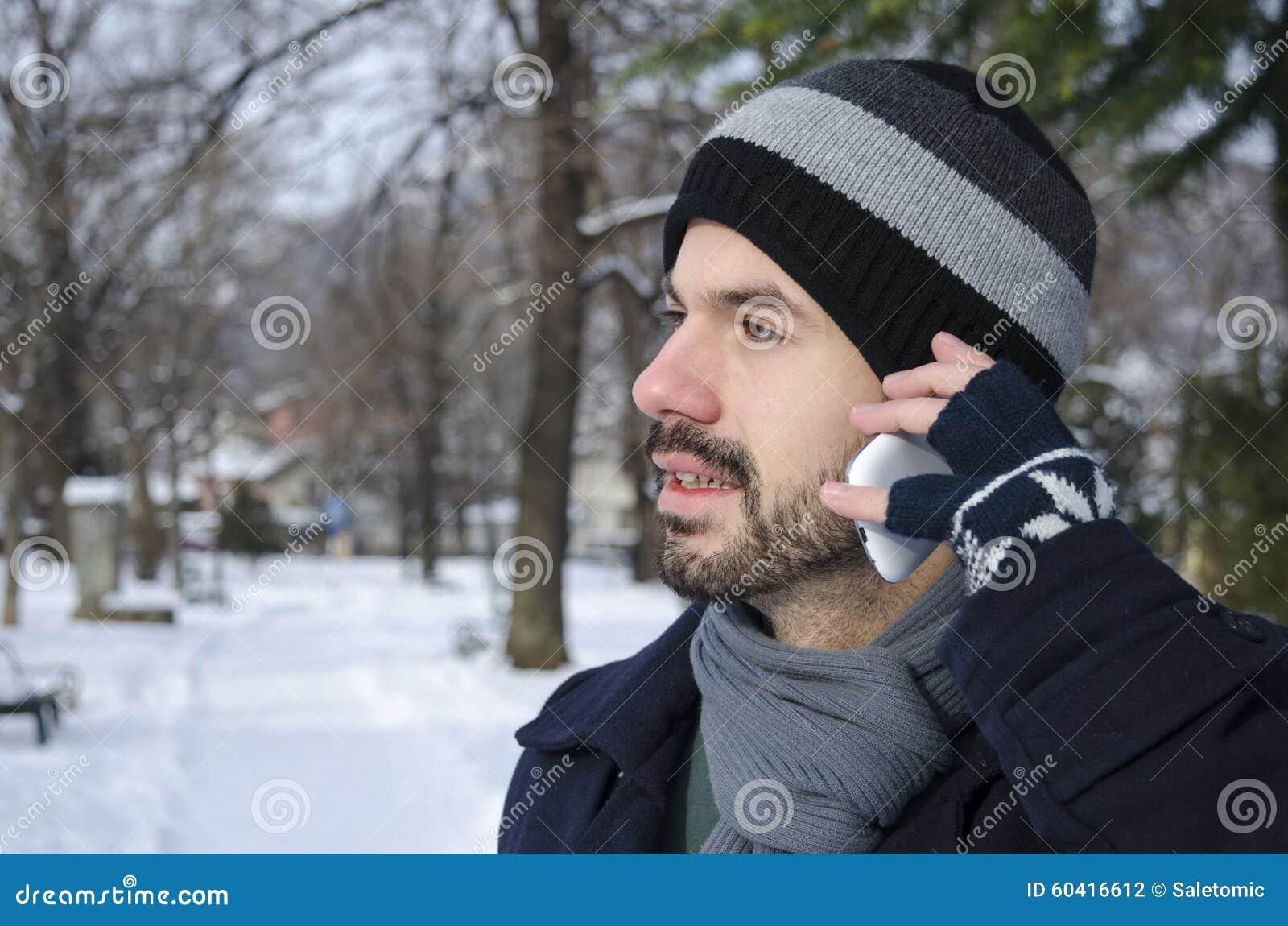 人谈话在一个智能手机在冬天