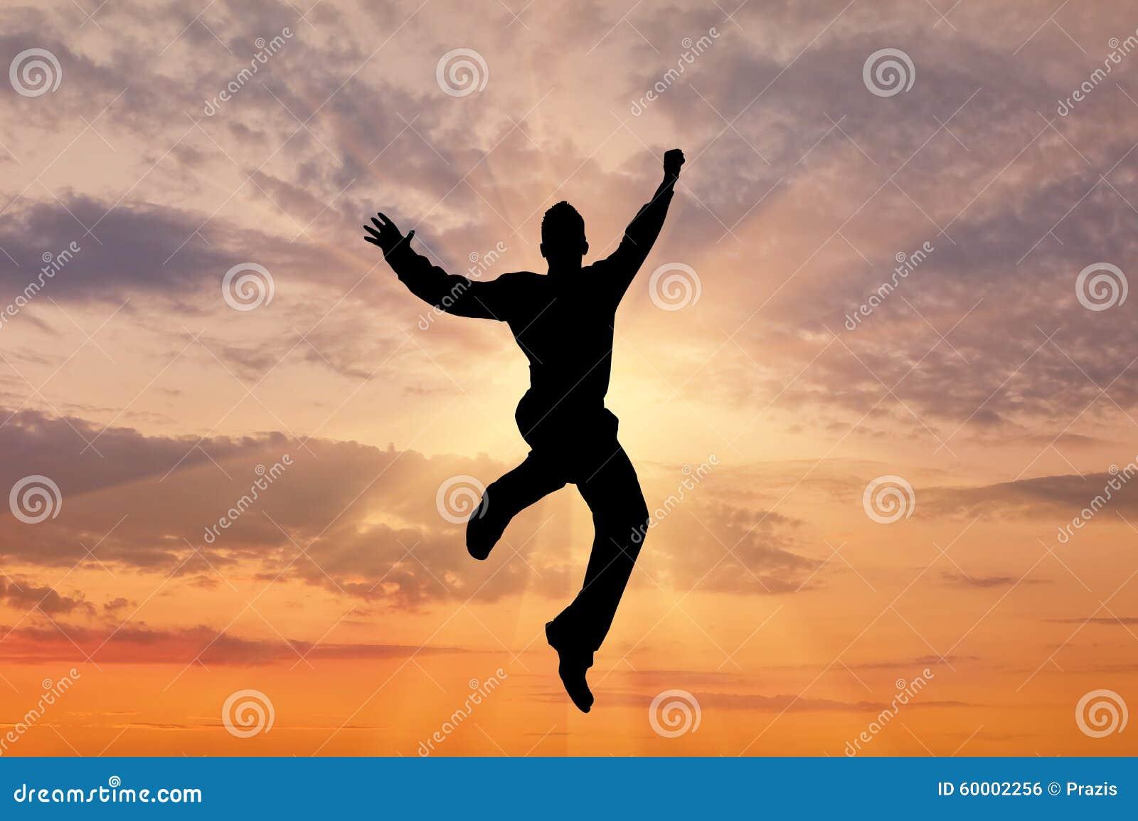 到达天空的企业概念金黄回归键所有权 在人跳跃的太阳天空剪影的