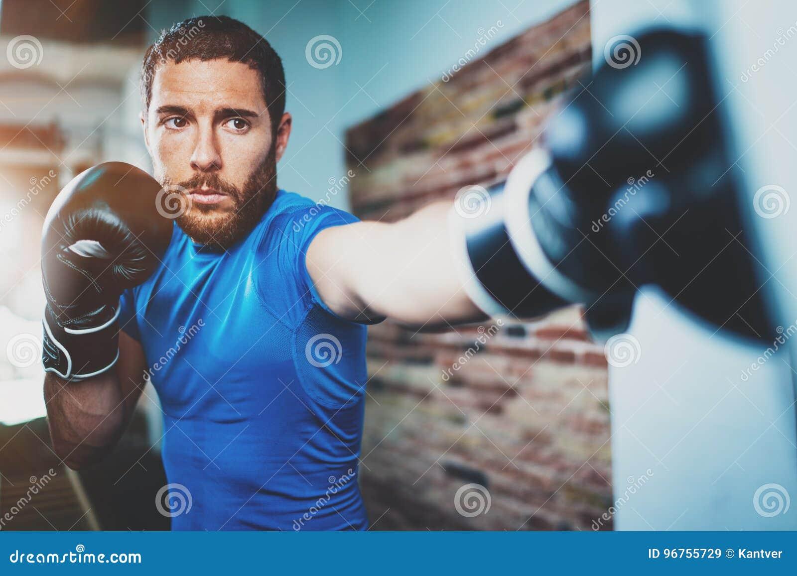 年轻人运动员在健身健身房的拳击锻炼在被弄脏的背景 艰苦训练运动的人 脚踢拳击概念