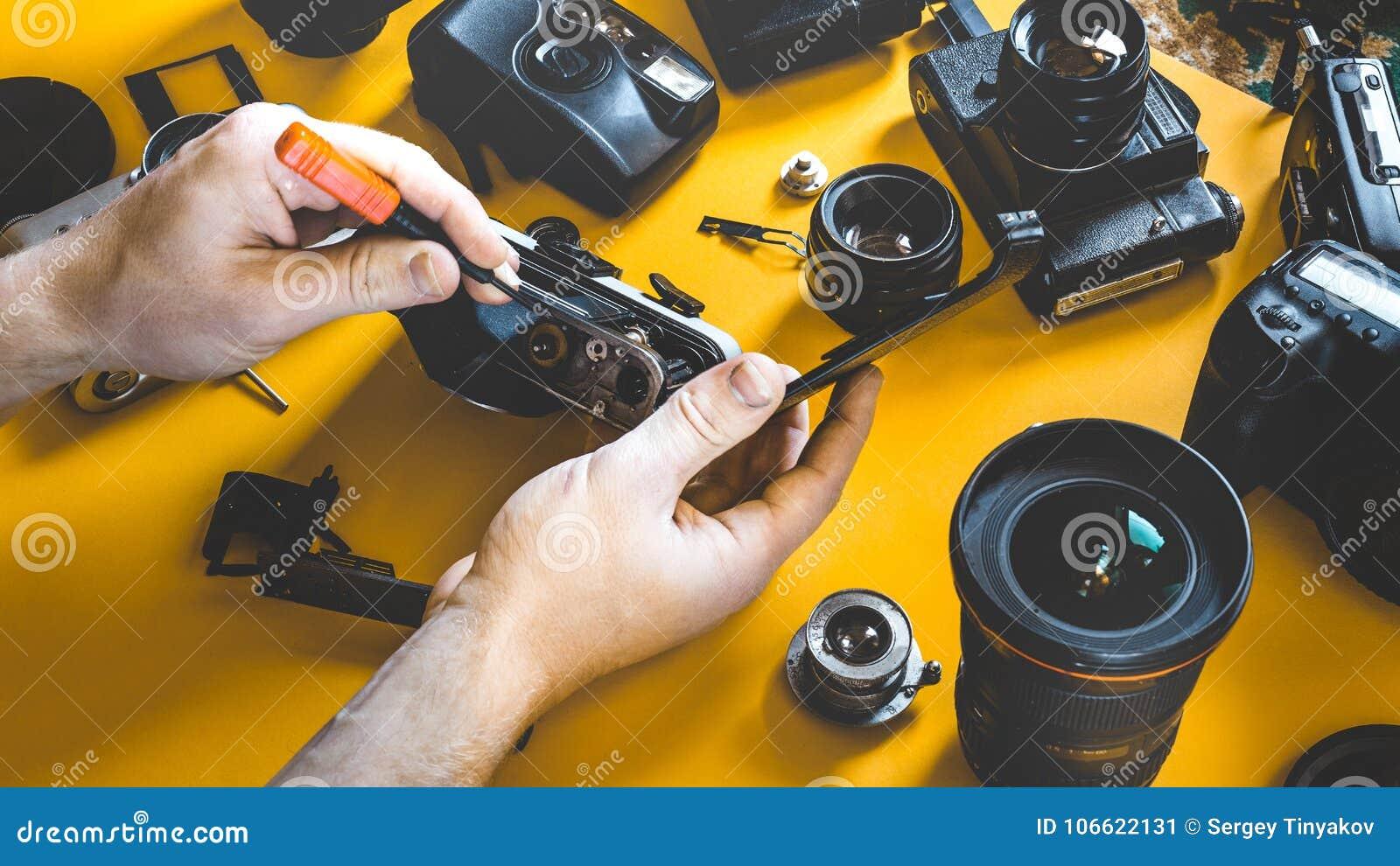 人递修理打破的影片照相机,照片工作场所