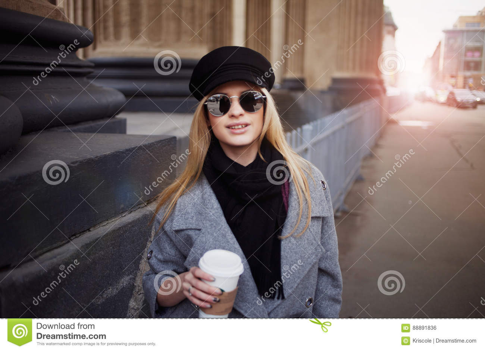 年轻人,熟悉内情和有吸引力白肤金发一个时髦的帽子的走在城市附近用咖啡去的,女孩和一件灰色外套
